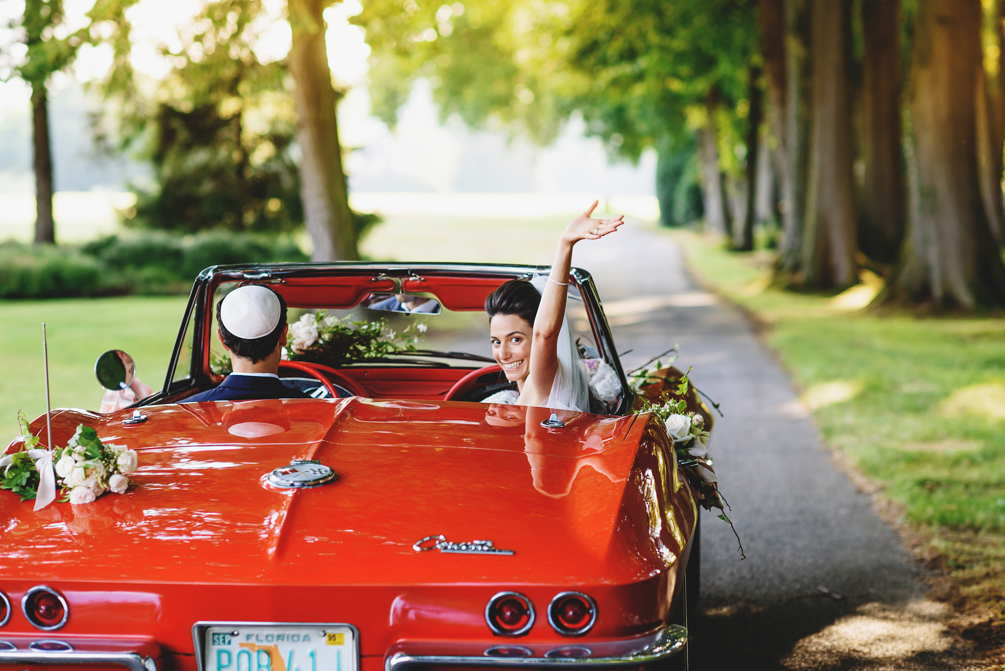 bride waves goodby in red convertible Corvette - photo by Ross Harvey