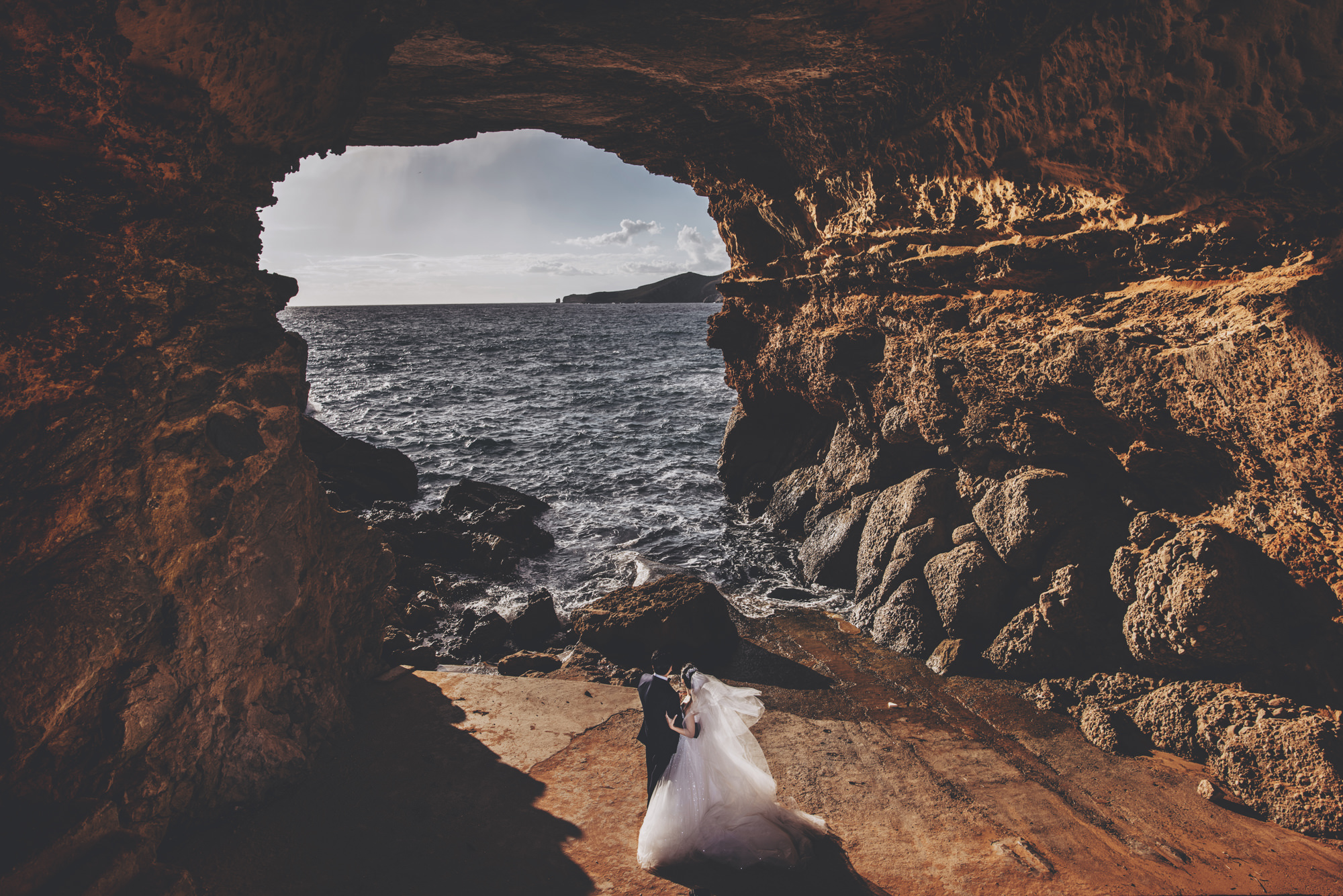 Couple look out at ocean through rock cave - photo by Look Fotographica