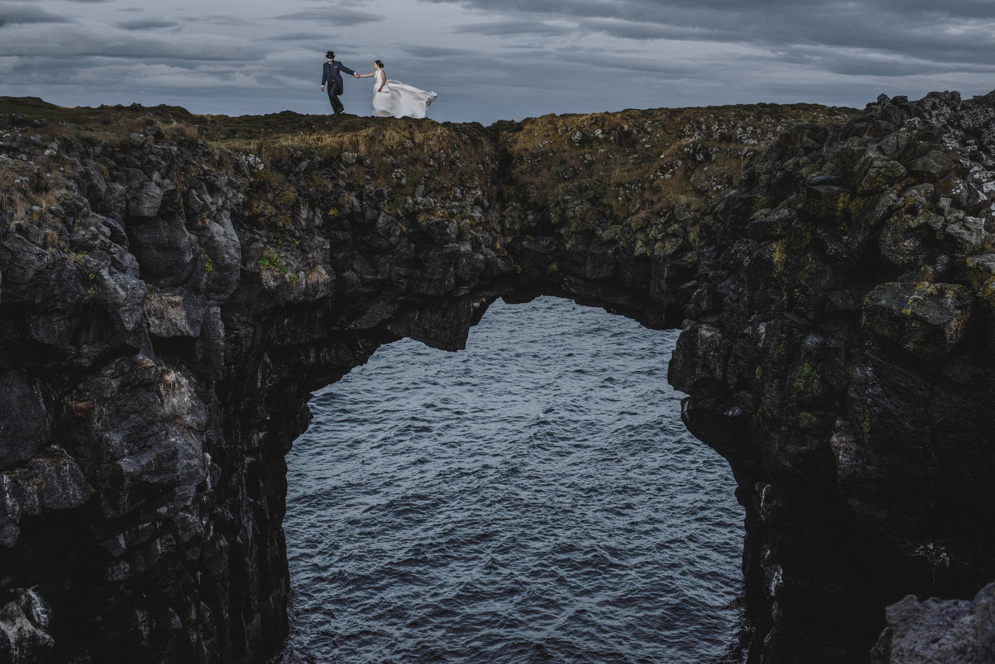 Couple make their way across arched bridge over water - photo by Look Fotographica