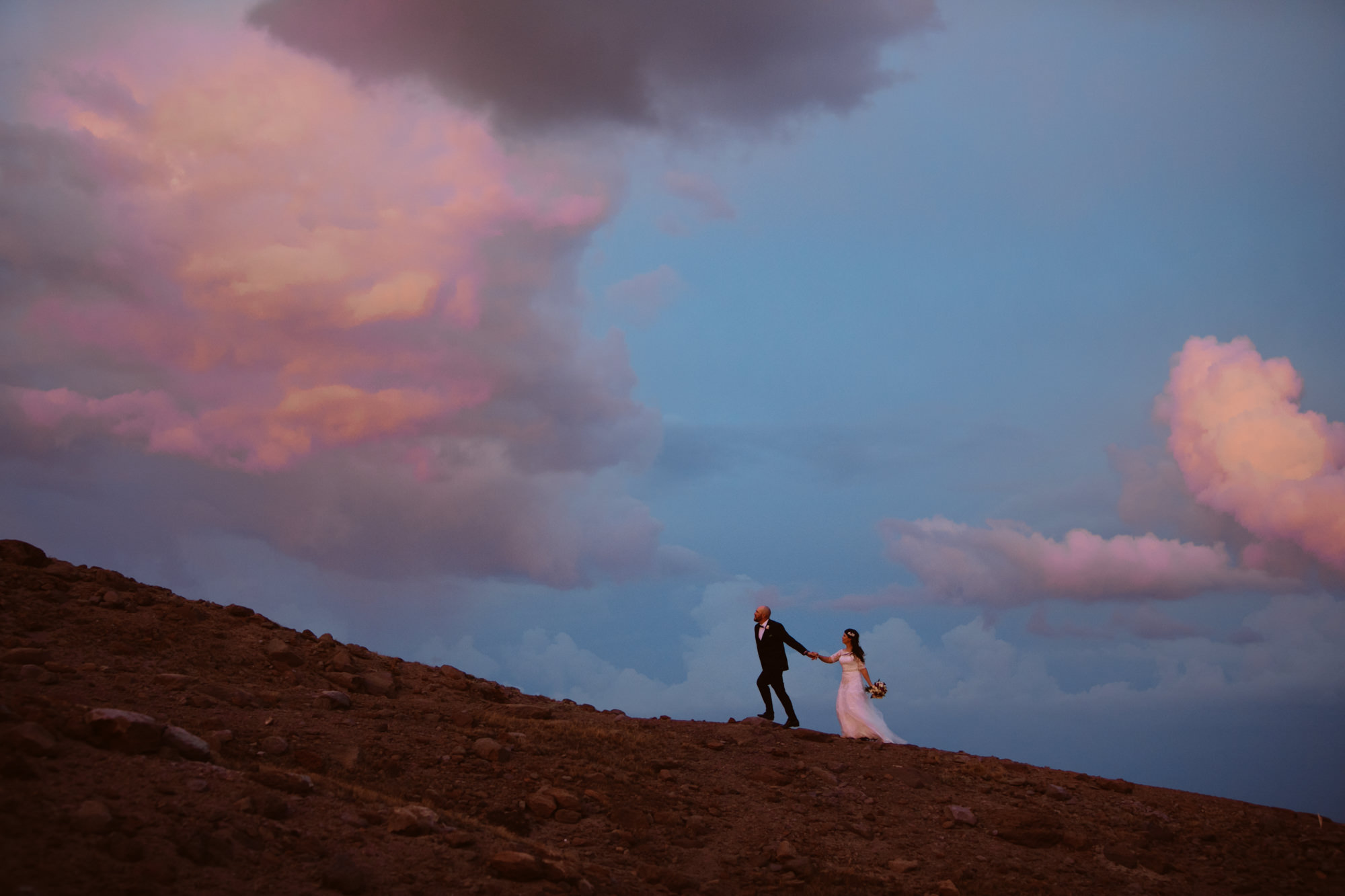 Couple makes their way up mountain during pink sunset - Jessica Hill Photography