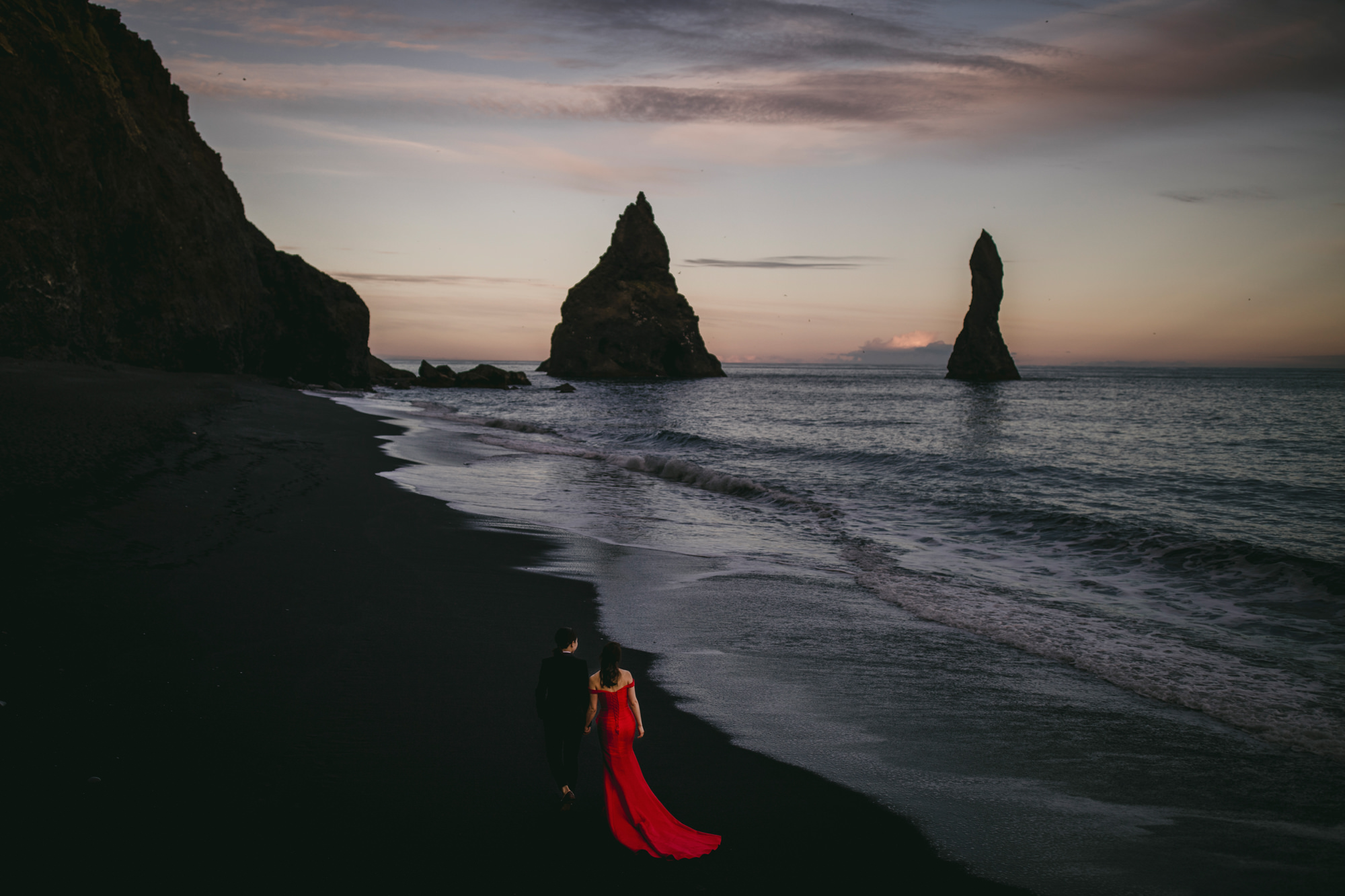 Couple on beach bride wearing red silk A-line - photo by McClintock Photography Agency