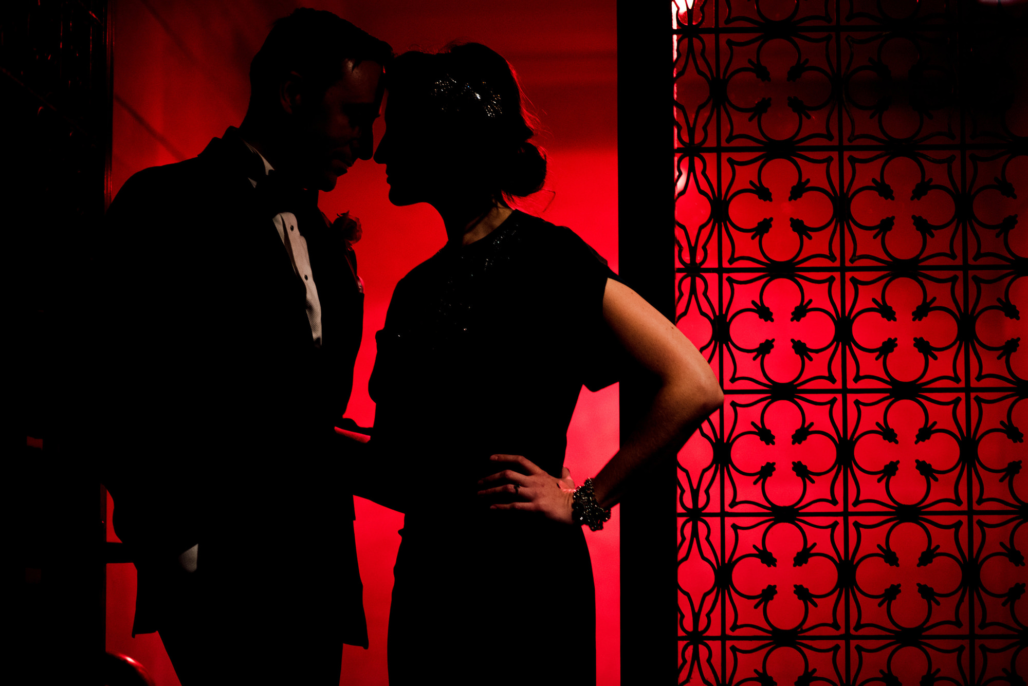 Semi silhouette of bride and groom against red wall, photo by The Brenizers