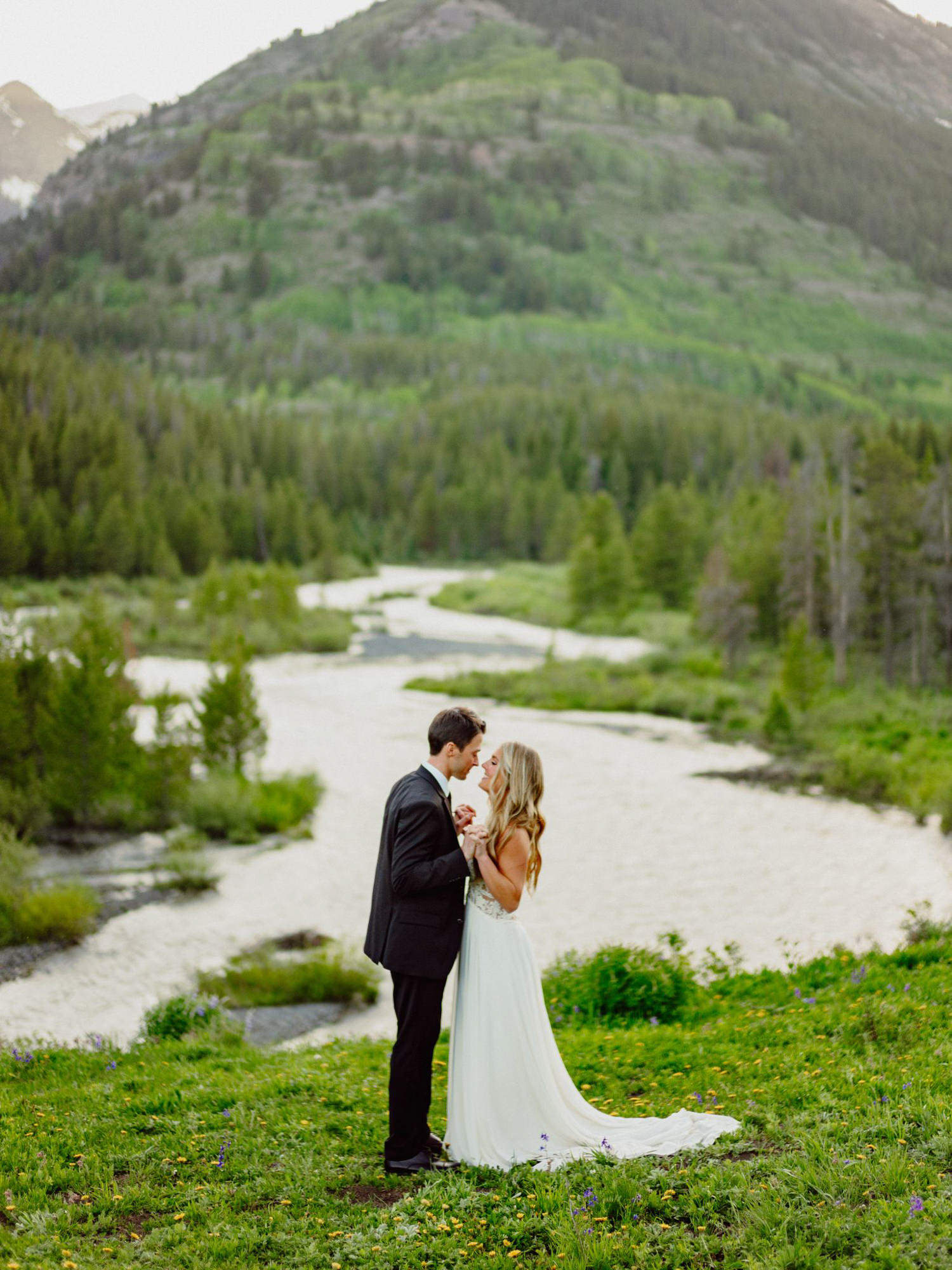 Couple hold hands against river and mountain scene, photo by Benj Haisch