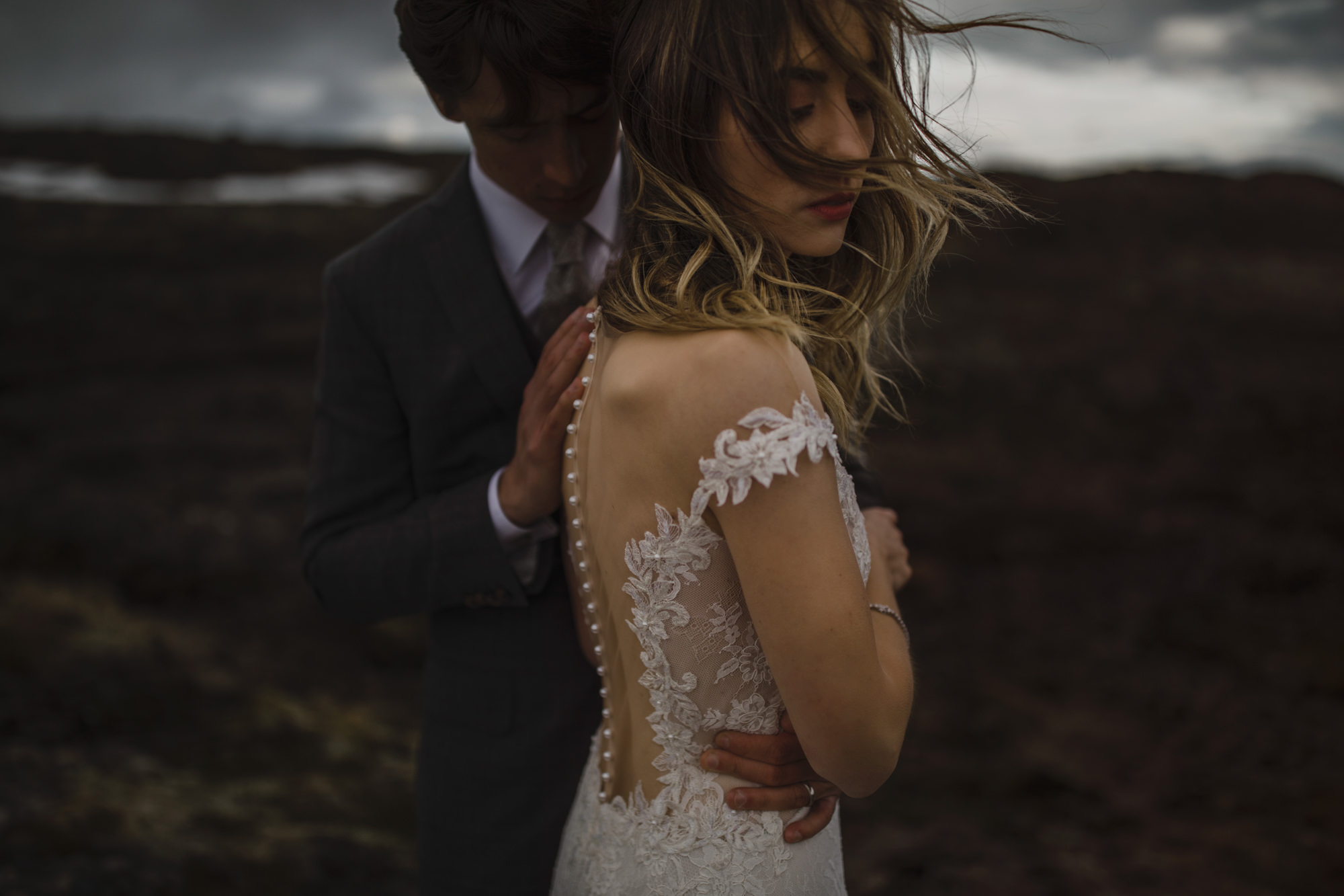 Couple portrait of bride in sheer back dress with buttons - photo by McClintock Photography Agency