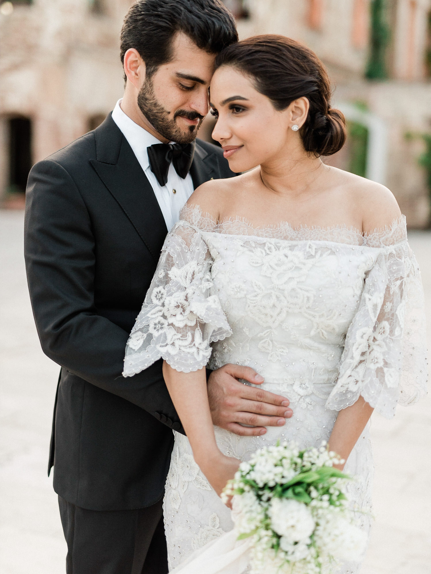 Groom holds his bride wearing applique lace gown - Gianluca Adovasio Photography