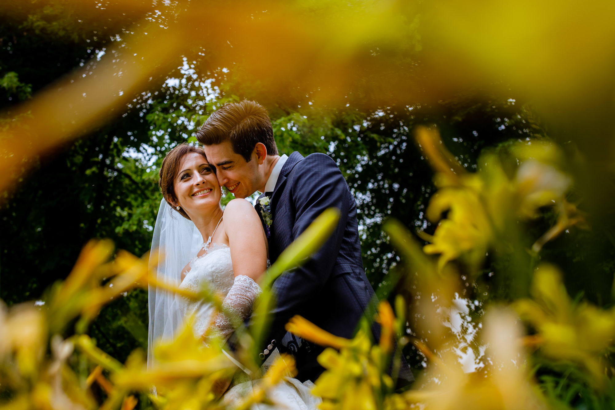 Couple portrait in yellow lily field - photo by Philippe Swiggers