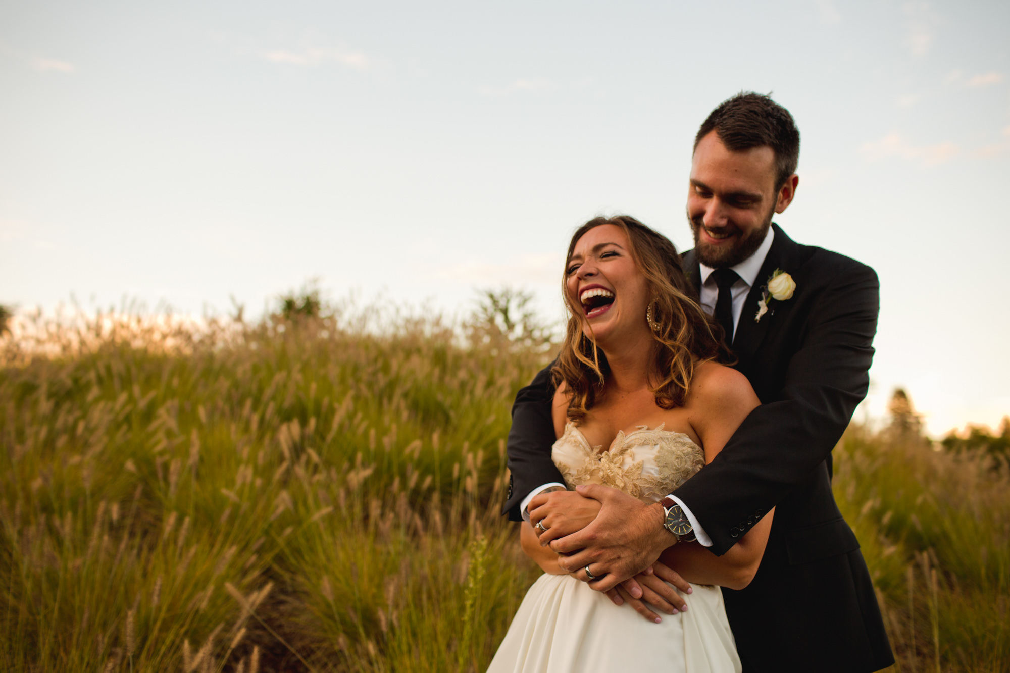 Groom holding laughing bride - Jessica Hill Photography