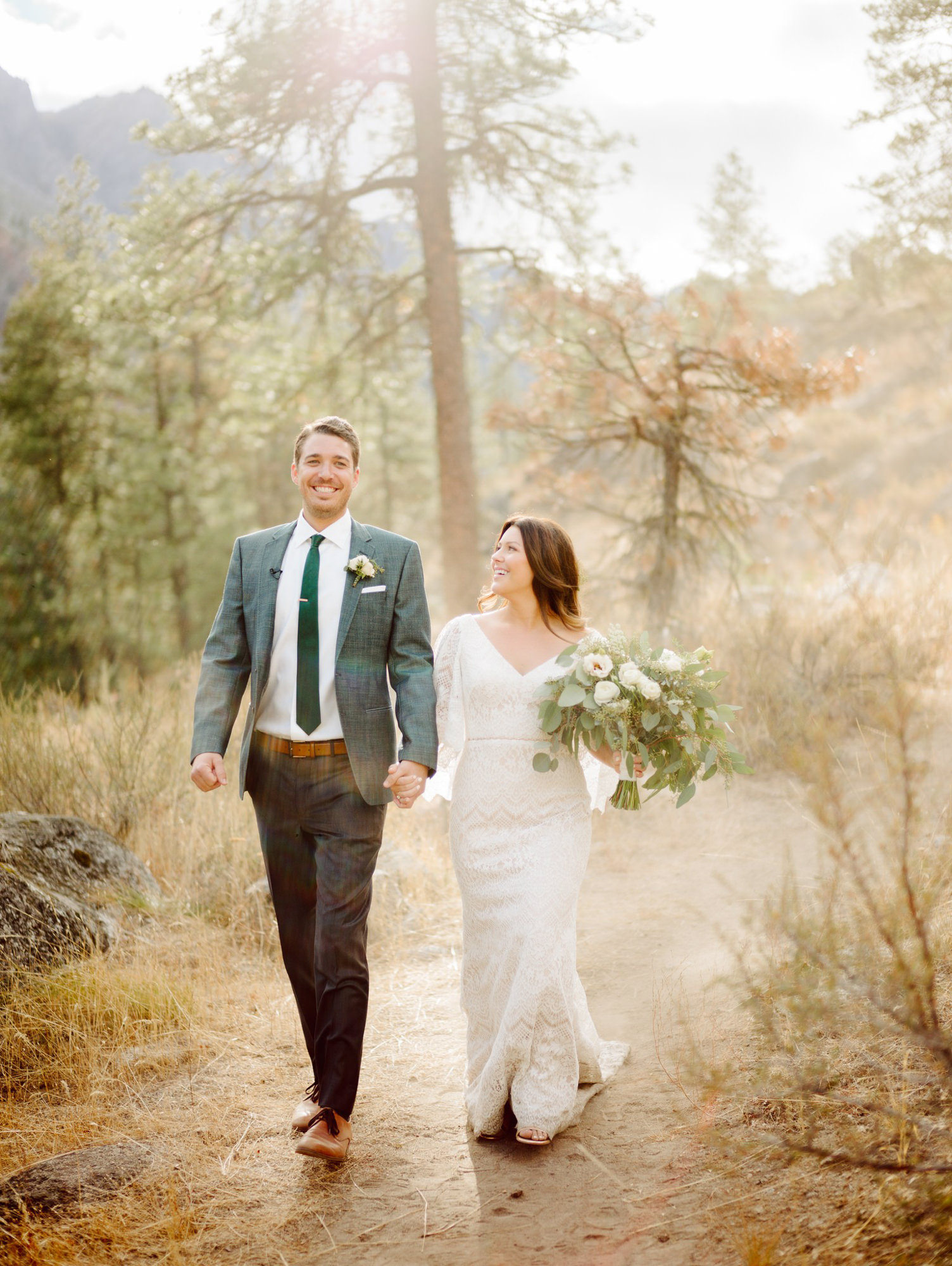 Bride in cape lace gown and groom in grey suit stroll through forest, by Benj Haisch