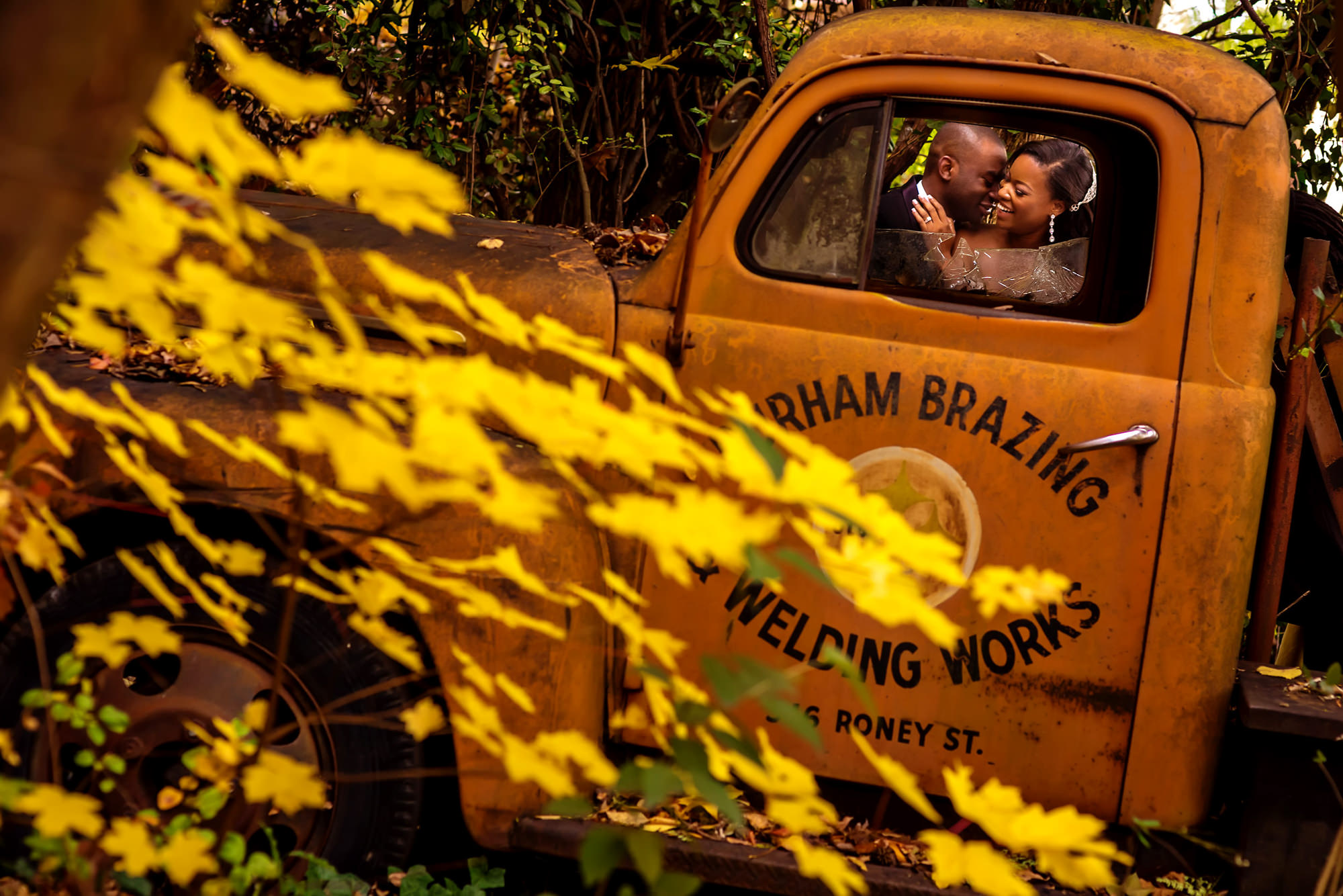Bride and groom in antique truck - photo by Alakija Studios