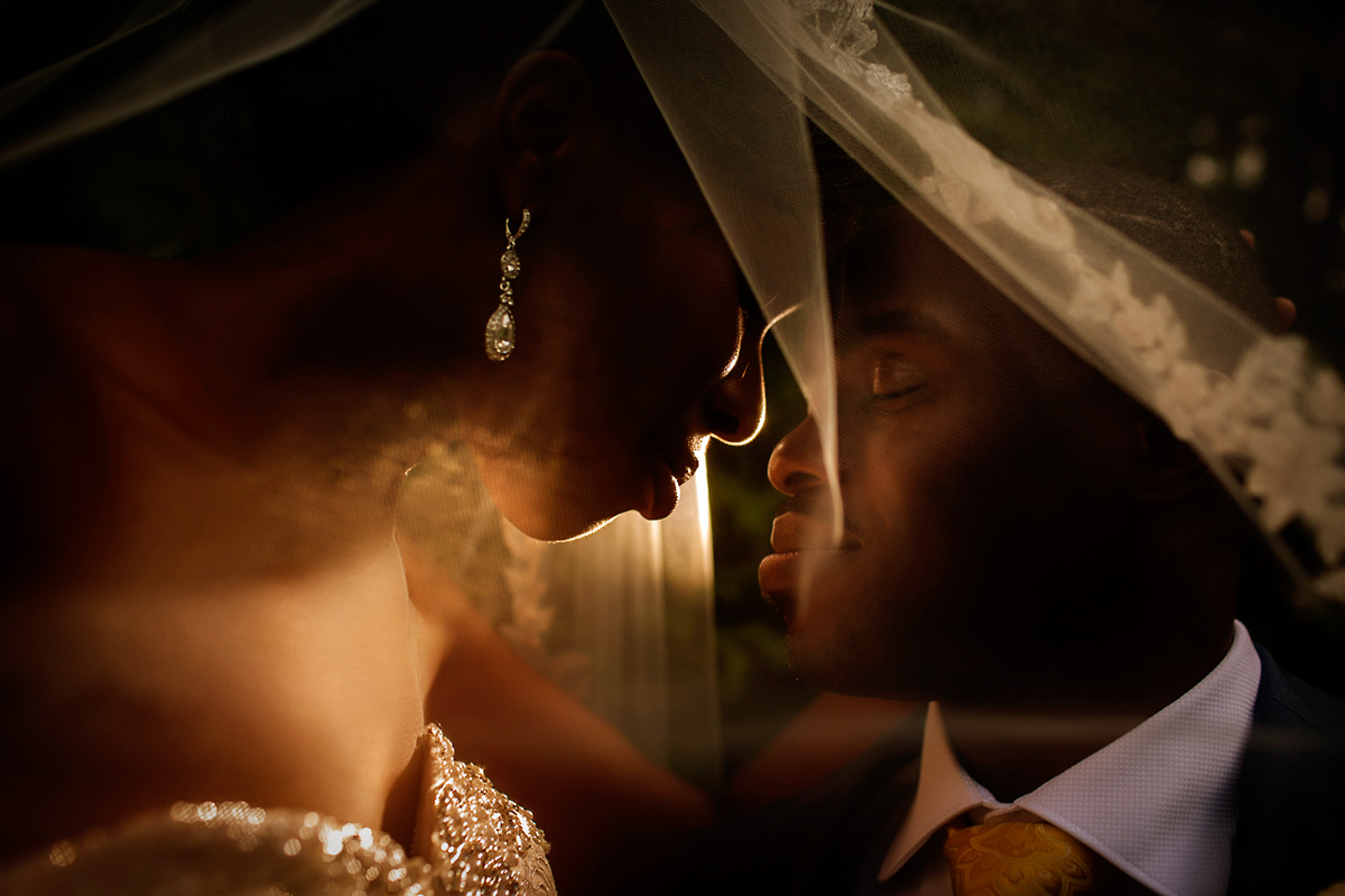 Couple prepares to kiss under veil - photo by Alakija Studios