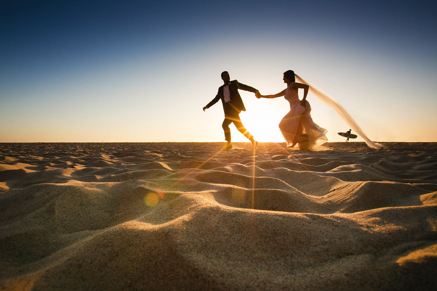 Partial silhouette of bride and groom running on beach by Callaway Gable