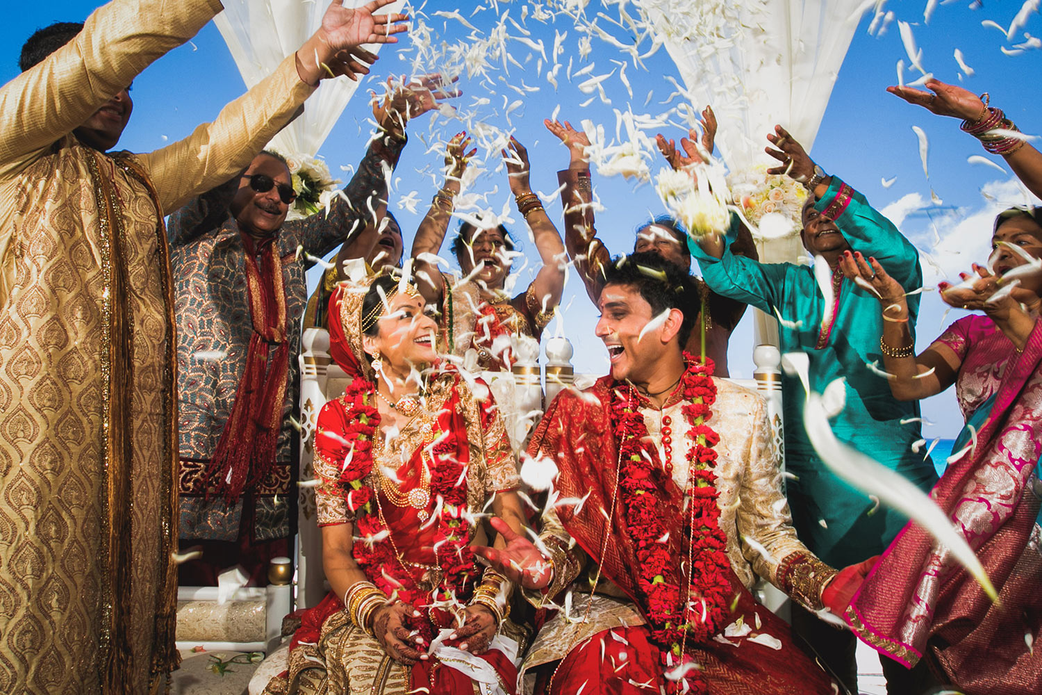 Indian couple showered with flowers at wedding ceremony by Callaway Gable