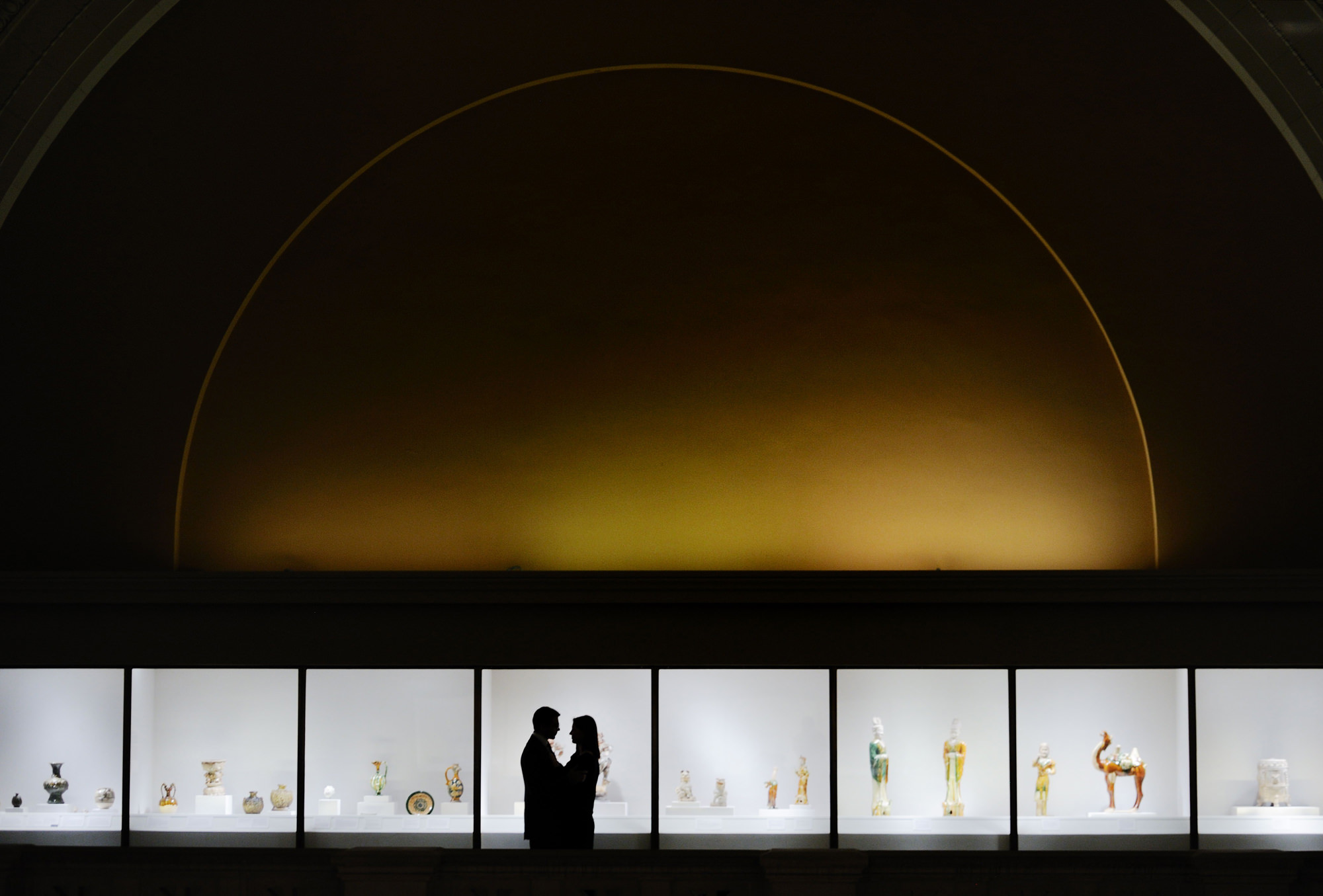 Silhouette of couple against sculpture exhibit, photo by The Brenizers