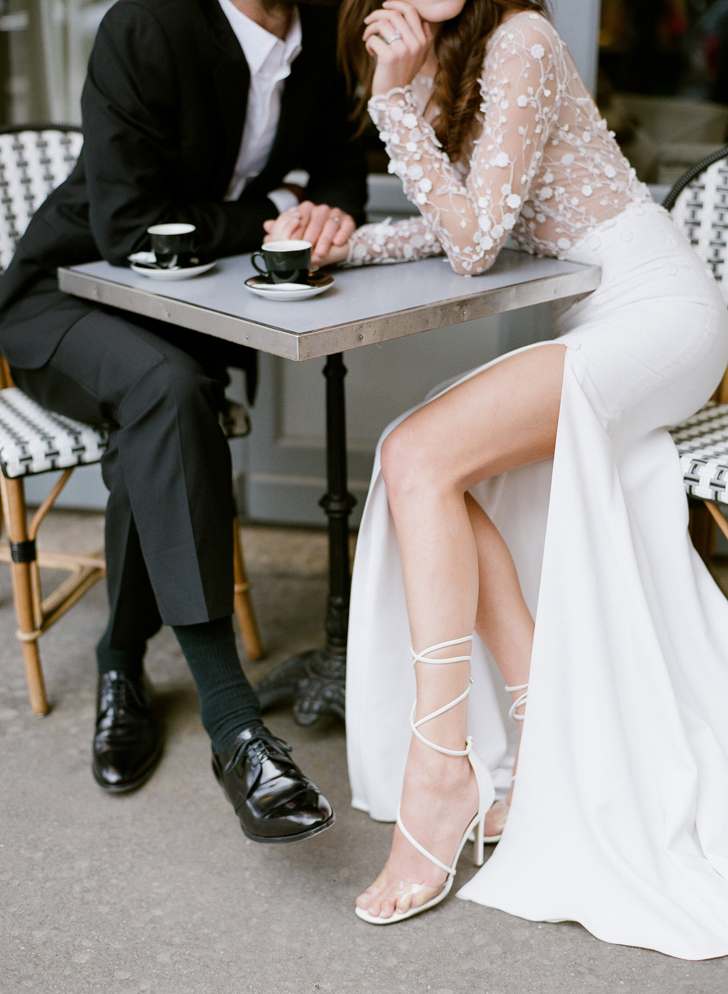 Sexy photo of couple sitting at cafe, bride with thigh-high slit skirt - Greg Finck Photography