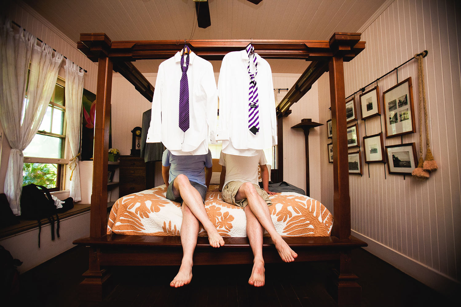 Grooms sit behind shirts and ties on four poster bed - photo by Callaway Gable - Los Angeles