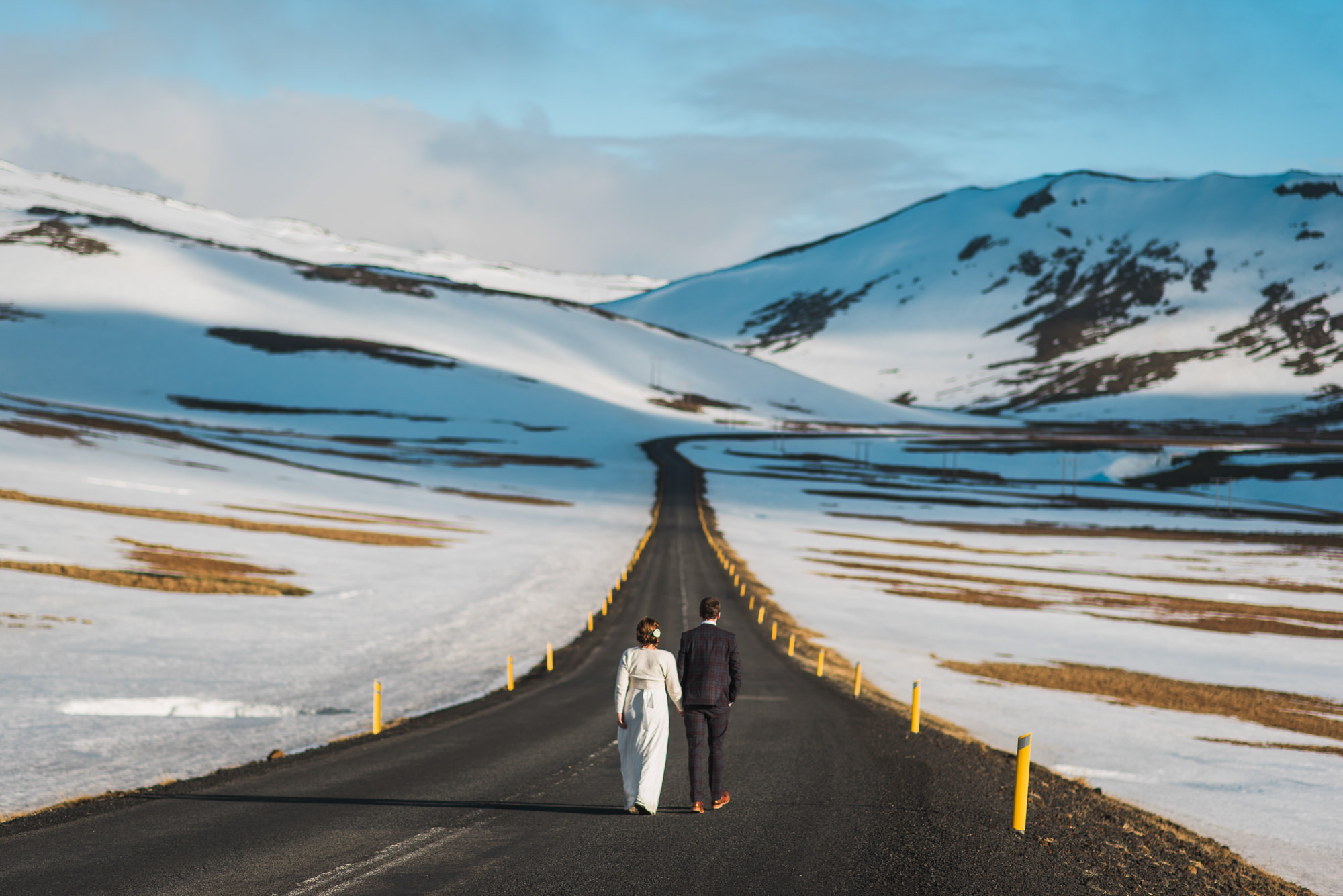 Couple walking down snowy tundra highway photo by Nordica Photography