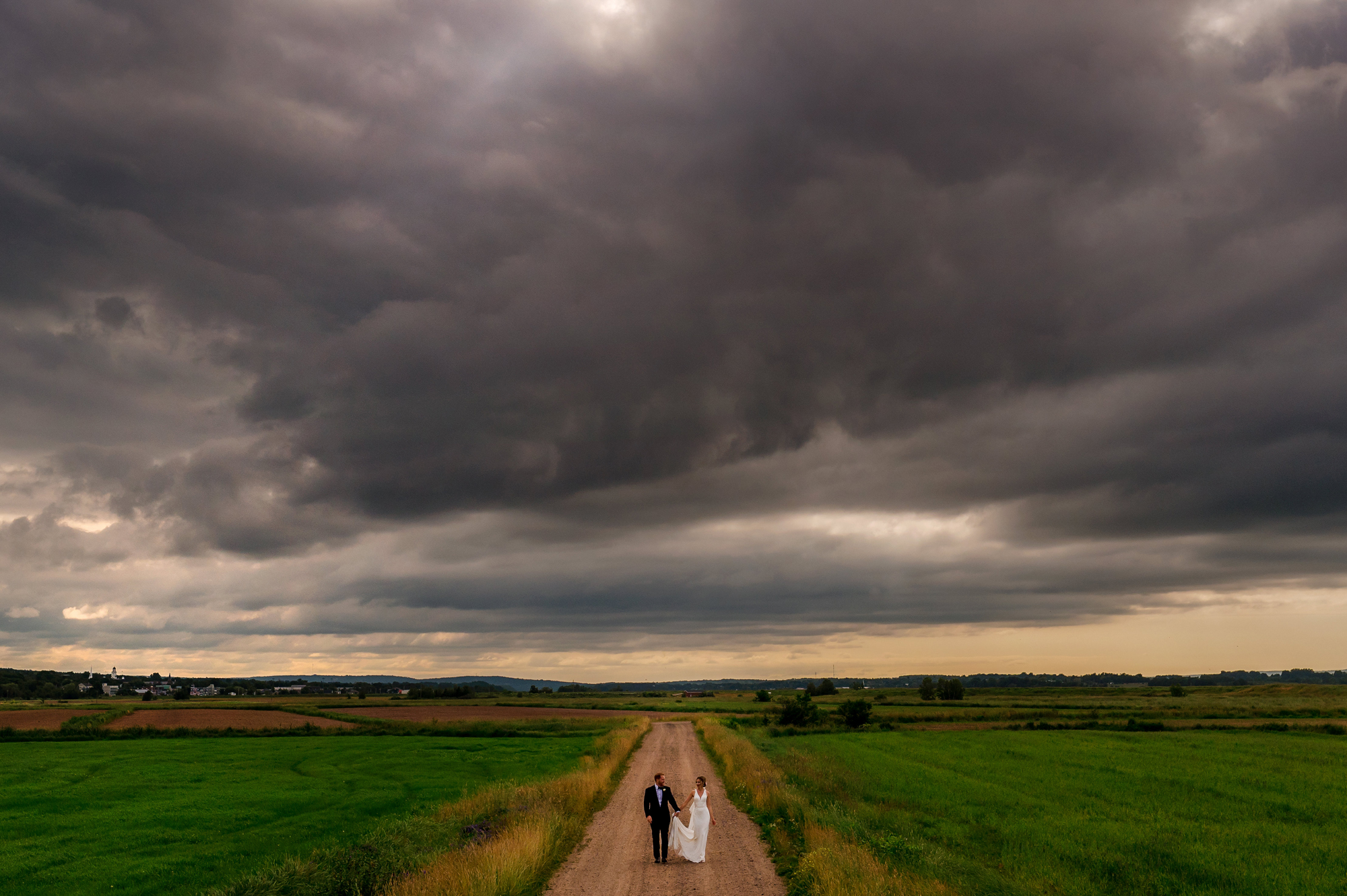 Couple walk under moody sky - photo by Cooked Photography