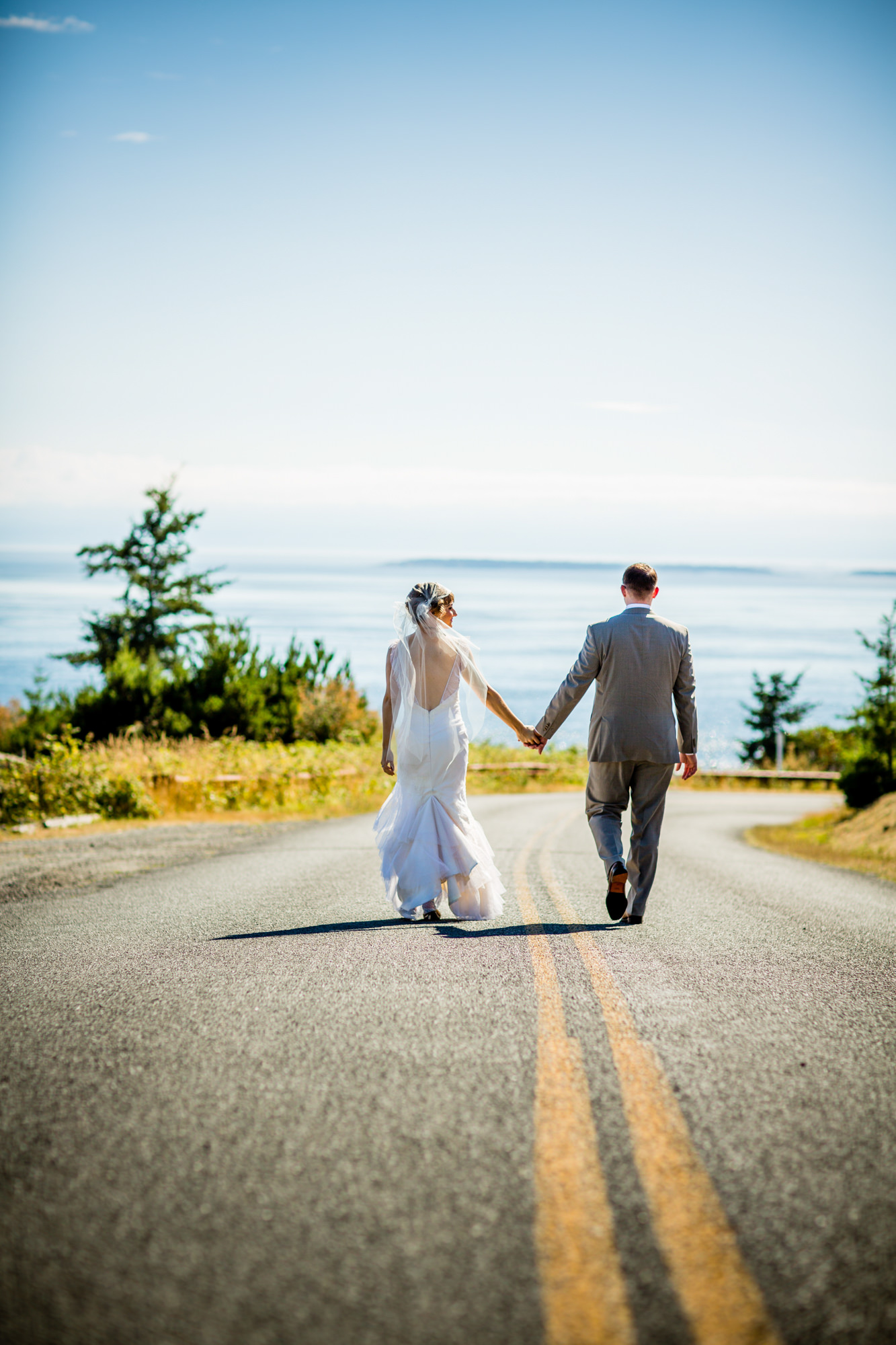 Couple walking down middle of the road on San Juan Island  - La Vie Photography