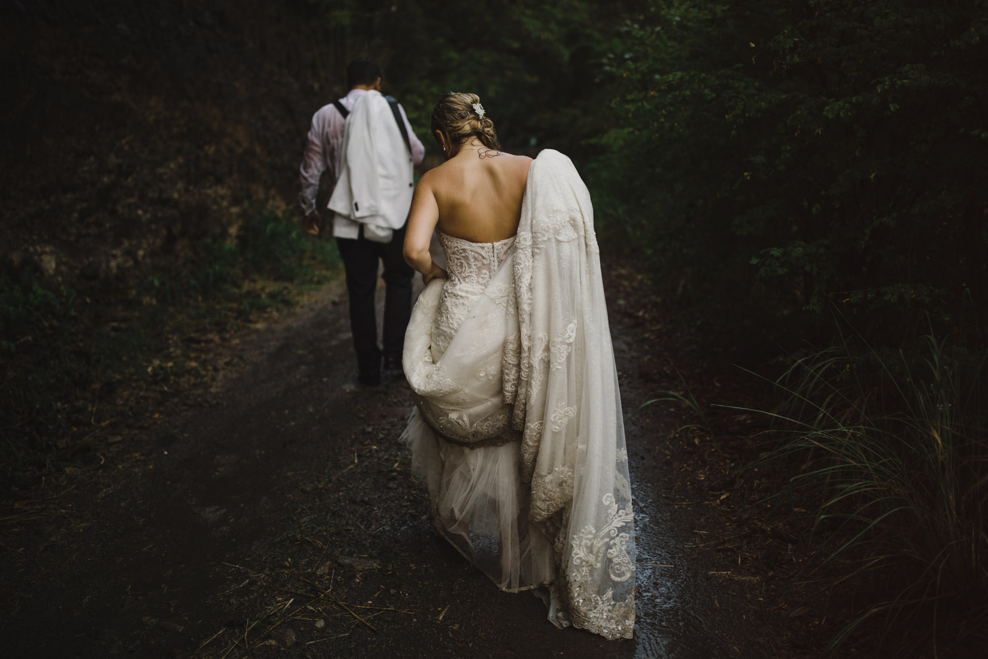 Couple walks down muddy road - photo by McClintock Photography Agency