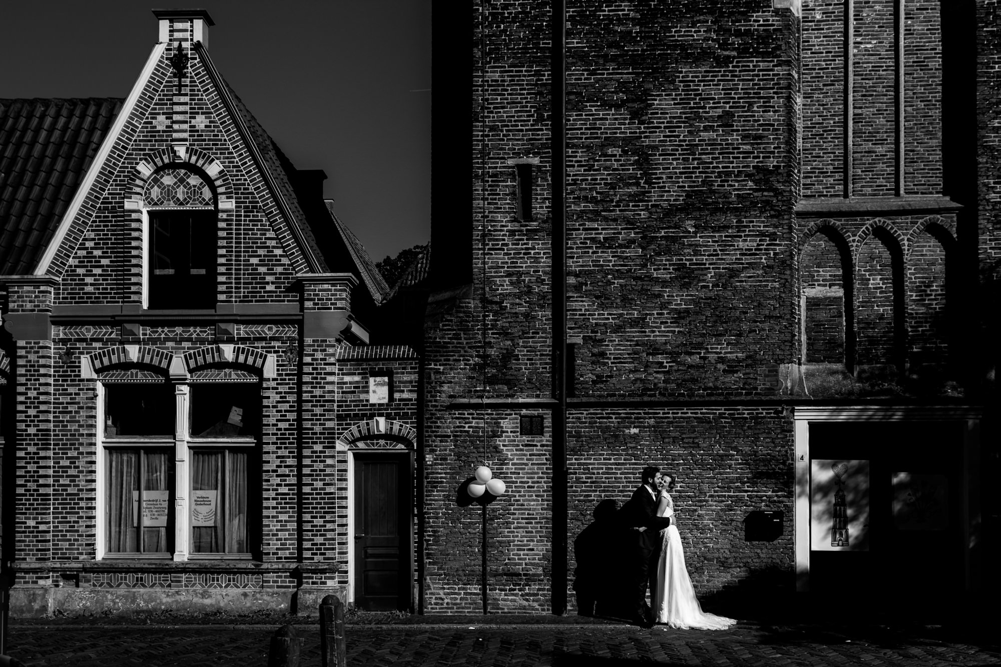 Bride and groom in front of old brick building photo by Fotobelle: Isabelle Hattink