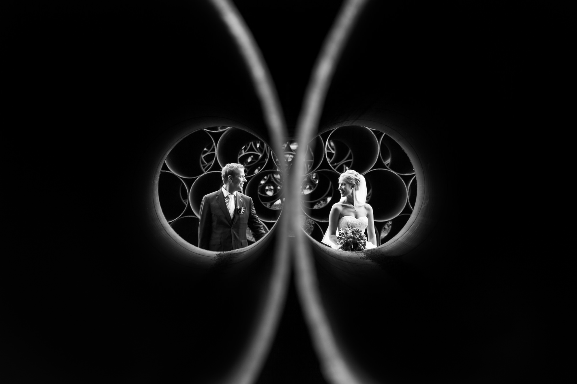 Creative portrait of couple through construction pipes photo by Fotobelle: Isabelle Hattink