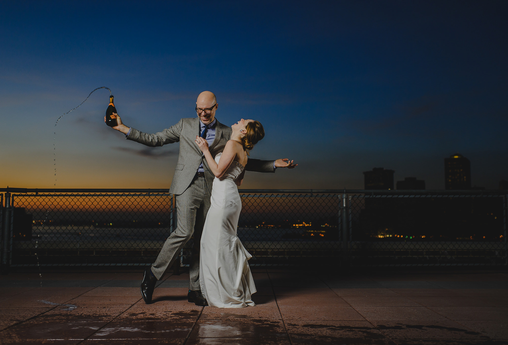 Fun photo of groom holding bottle of champagne dancing with bride, photo by The Brenizers