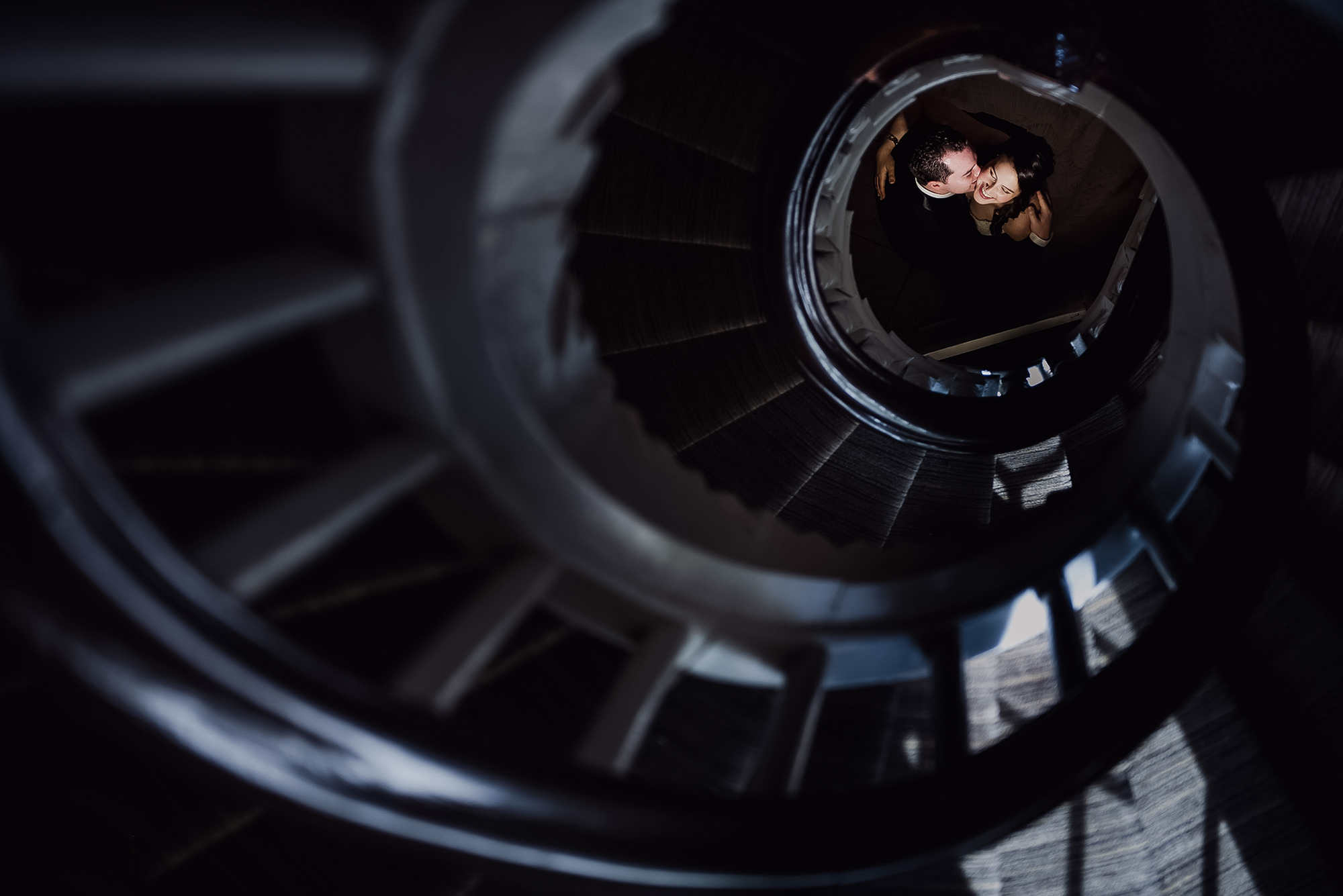 Creative portrait of couple at bottom of circular stairs - photo by The Brenizers - NYC