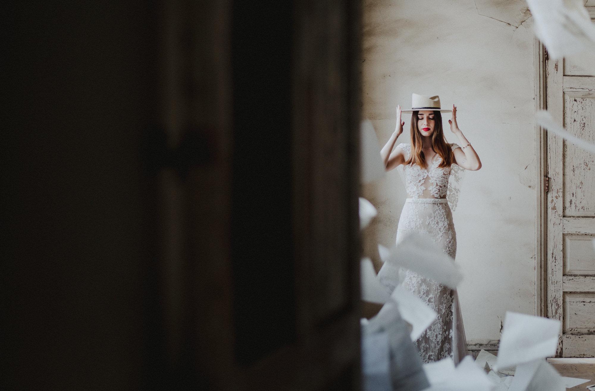 Creative portrait of bride wearing white hat by Fer Juaristi