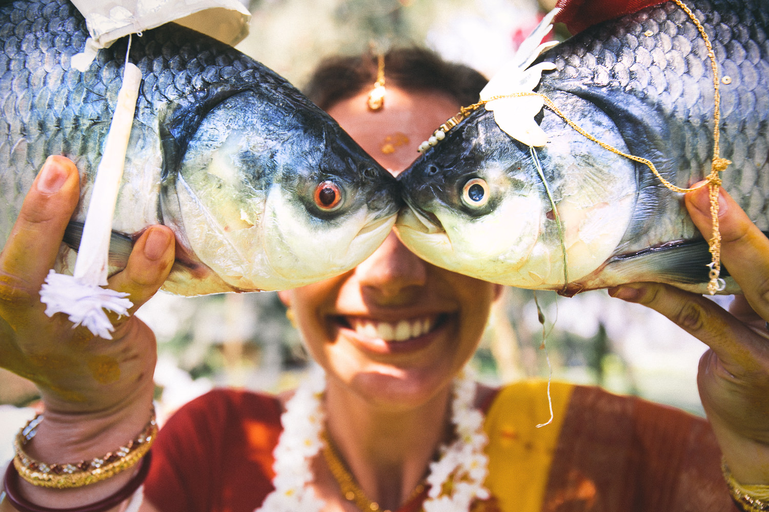 Fun photo of two fish in front of Indian bride, by Callaway Gable