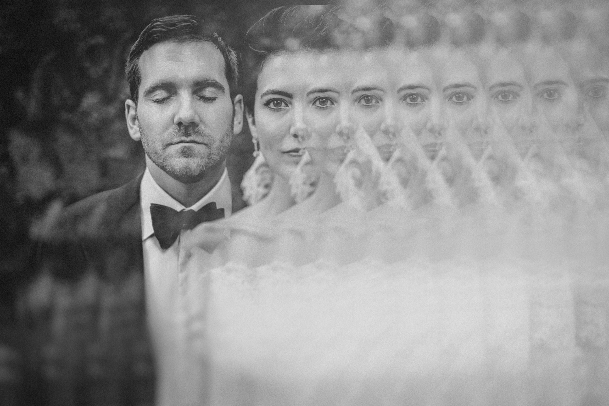 Back and white portrait of bride and groom taken through prism