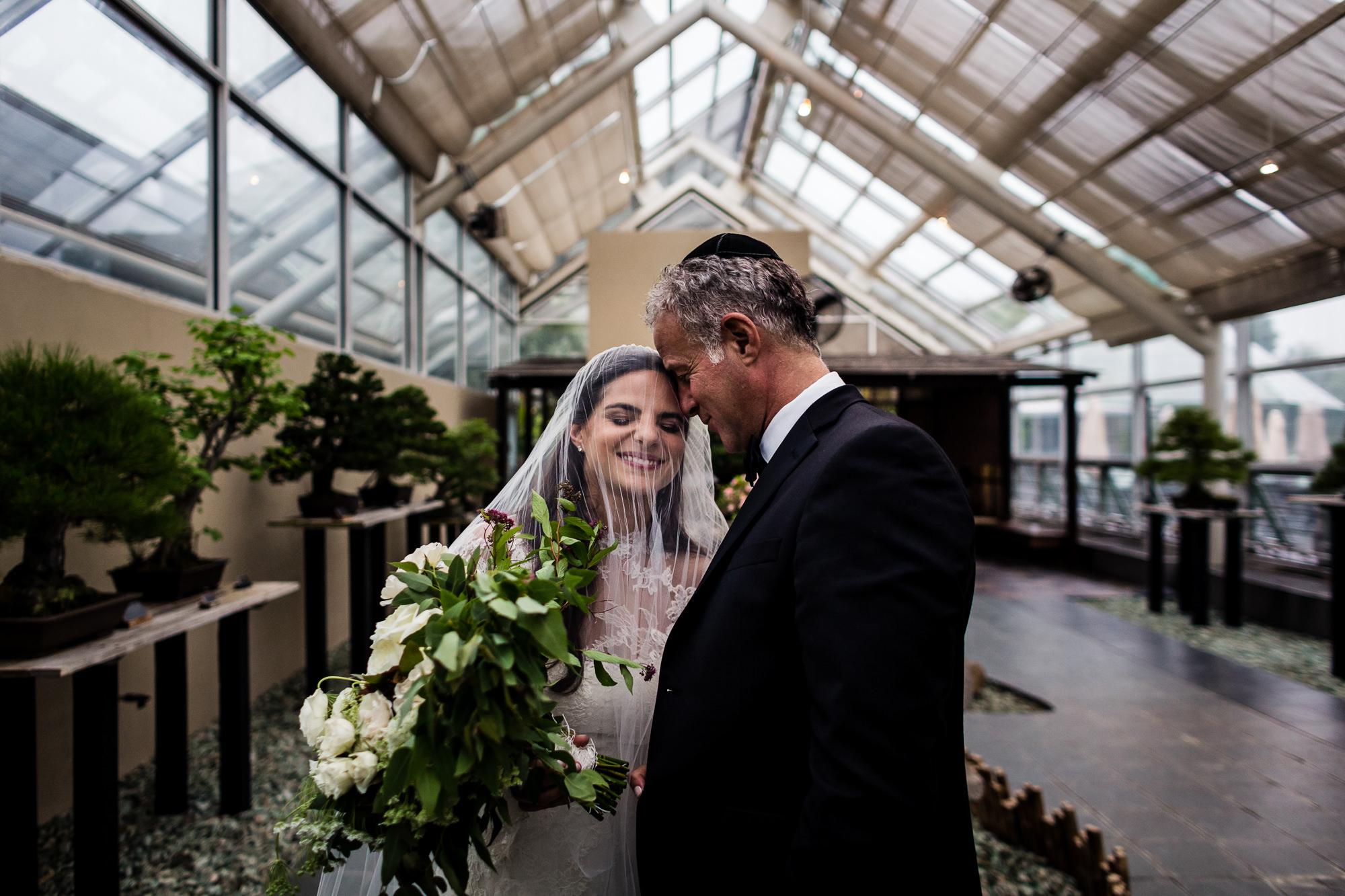 Dad embracing bride in long veil - photo by JAG Studios