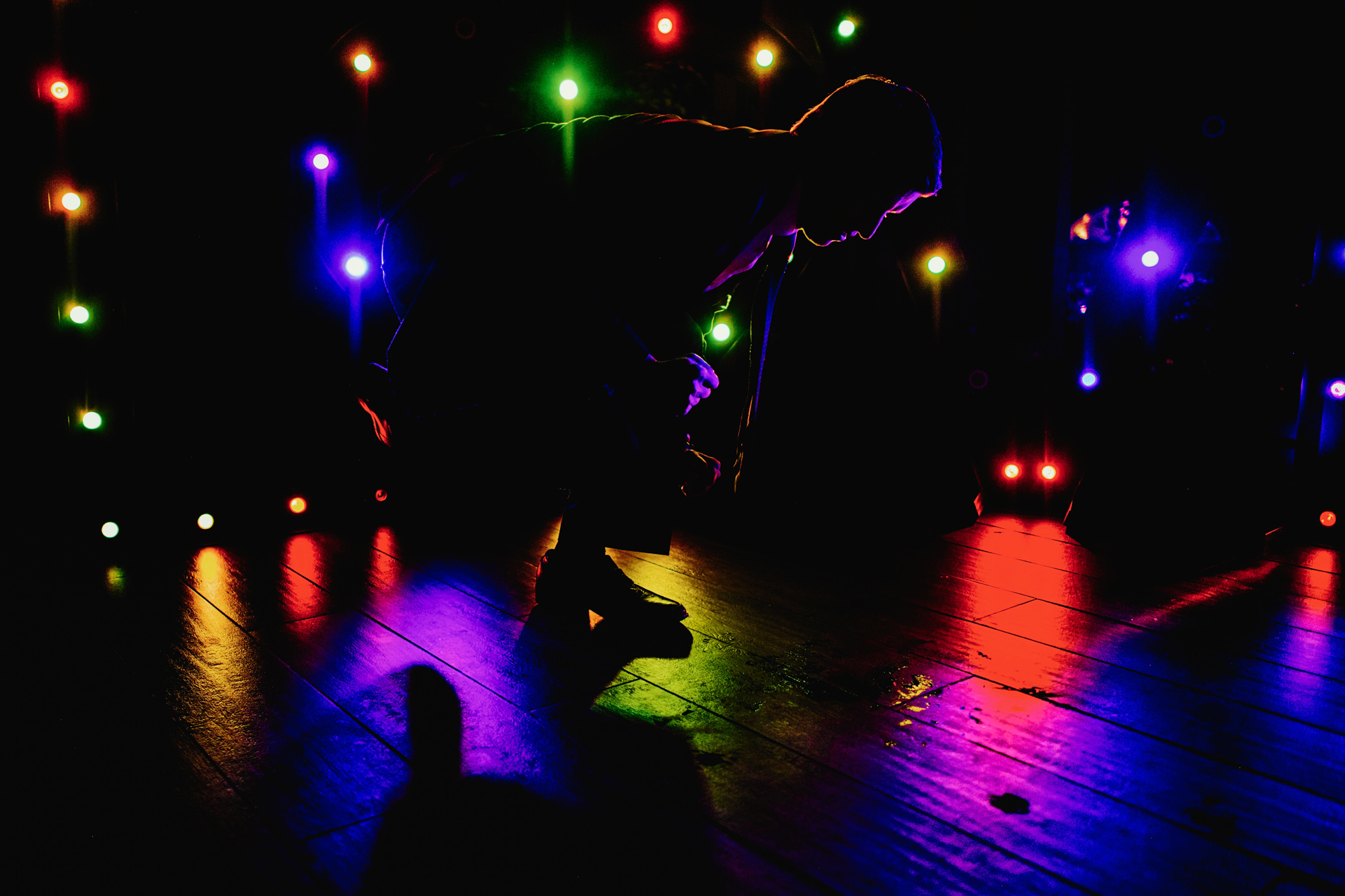 Silhouette of man dancing in colored light by Fer Juaristi