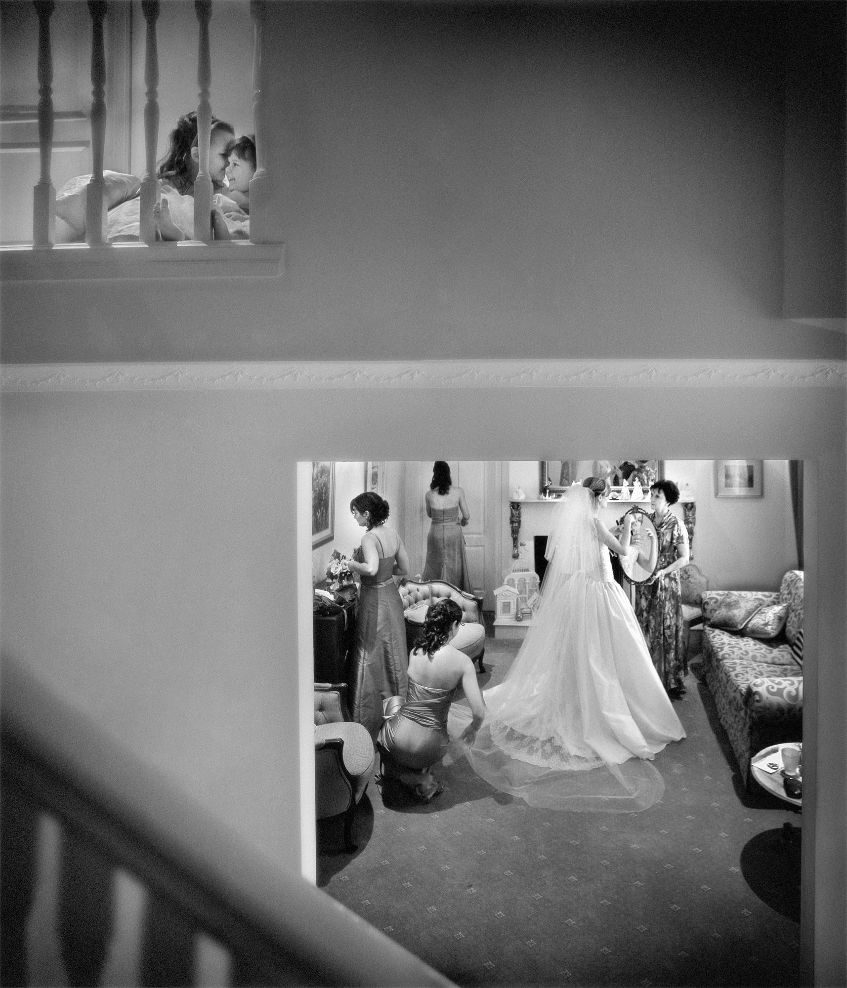 Story-telling photo of kids whispering while bride gets ready downstairs- Studio Impressions Photography