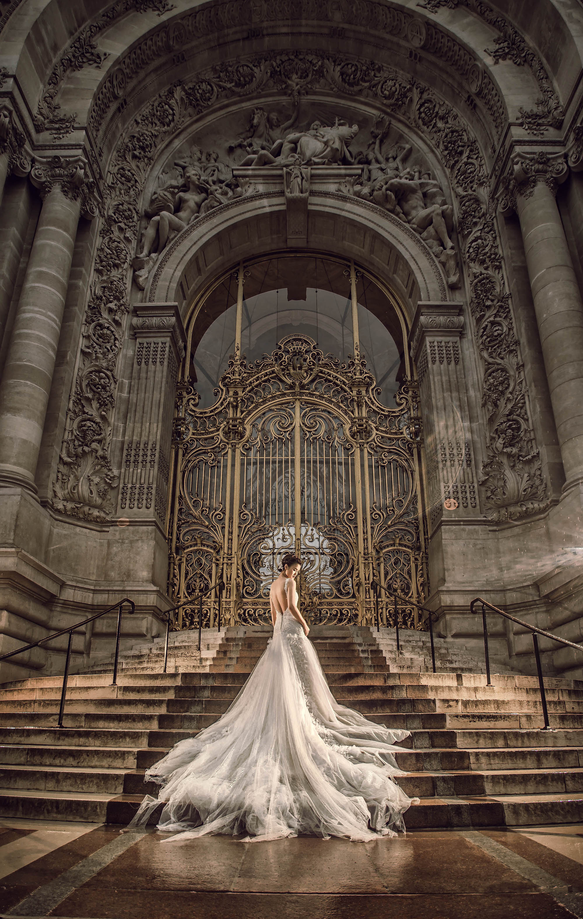 Dramatic bride in tulle and beaded gown in front of historic cathedral, by CM Leung