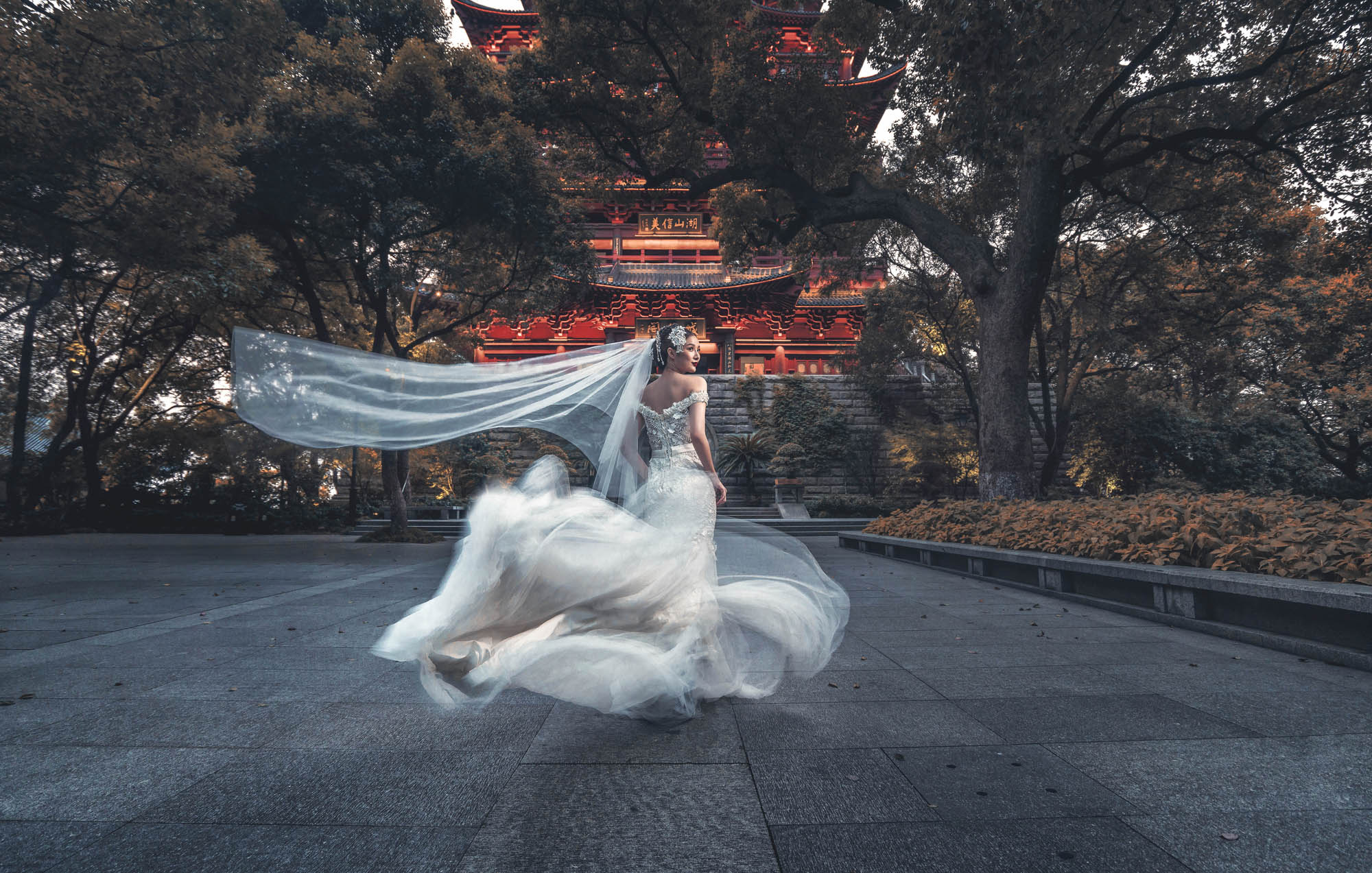 Bride in offshoulder beaded chiffon gown by Chinese temple, by CM Leung