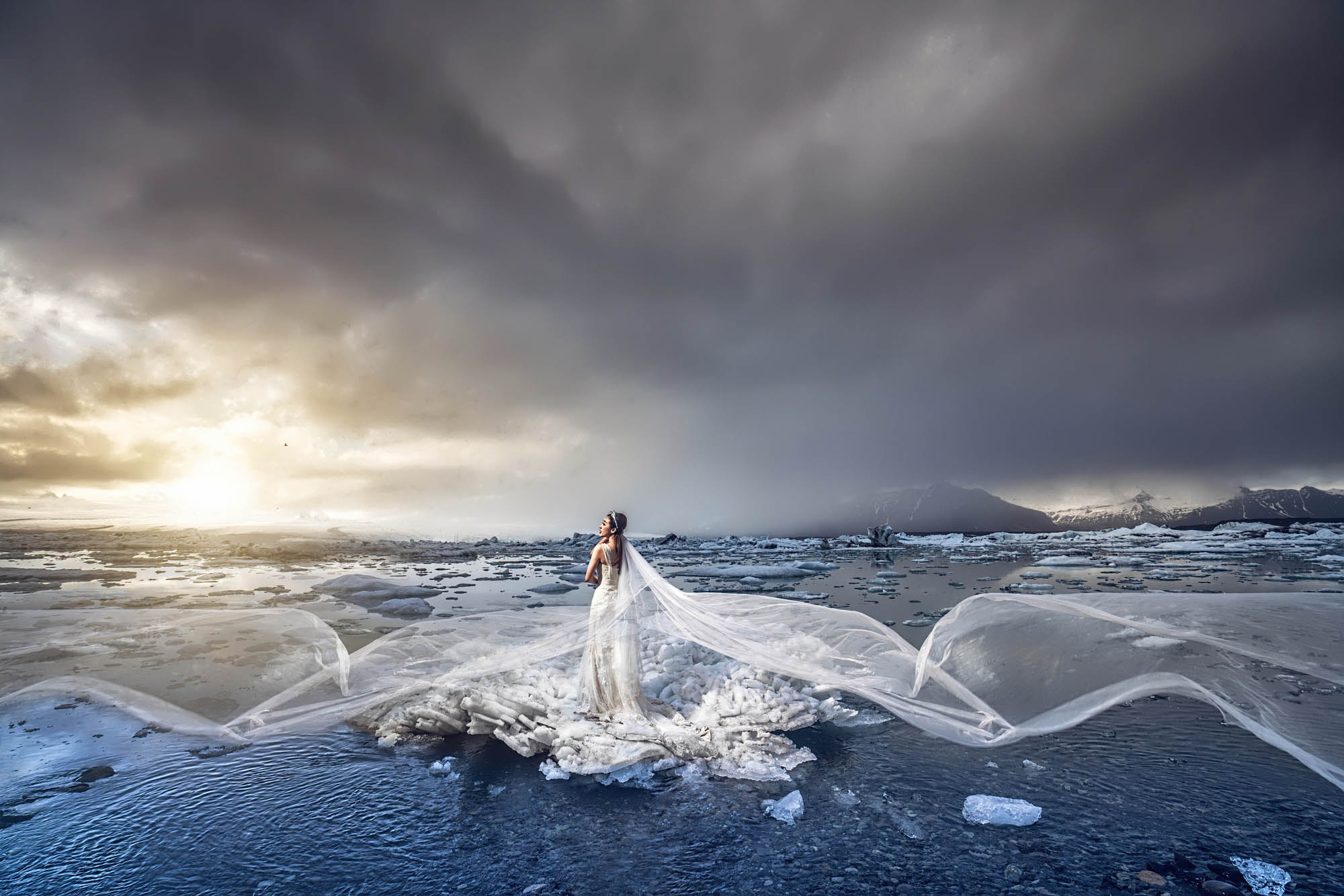 Dramatic bridal portrait with flowing veil by ice lake, by CM Leung