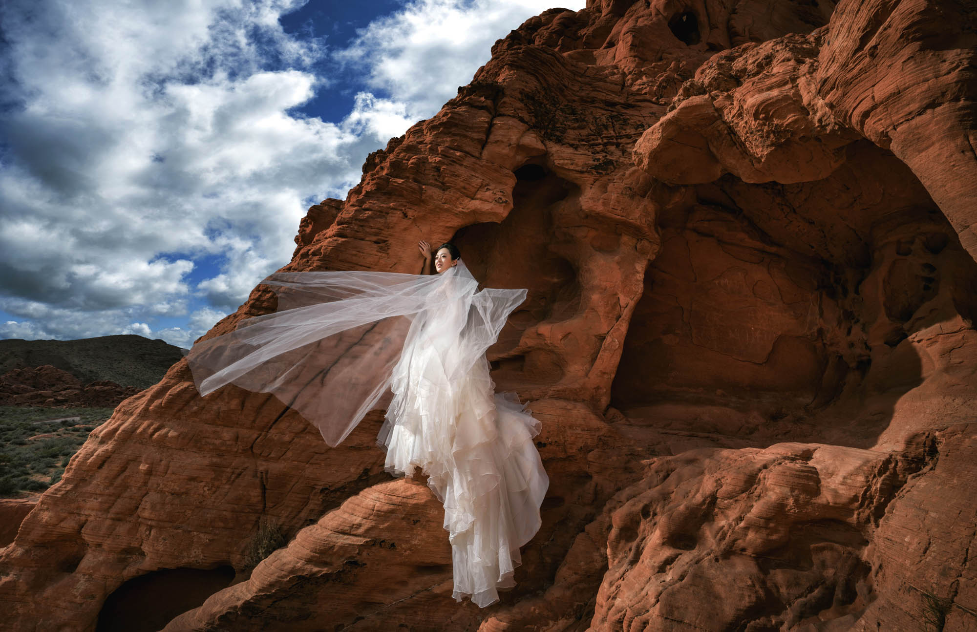 Bride in beautiful chiffon ruffled gown standing on red rock, by CM Leung