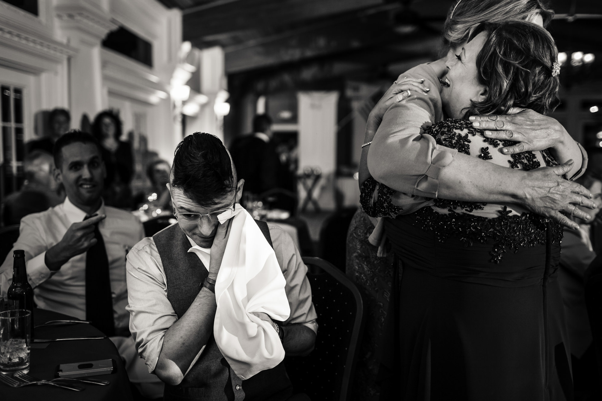 Emotional photo of hugs during reception - photo by JAG Studios
