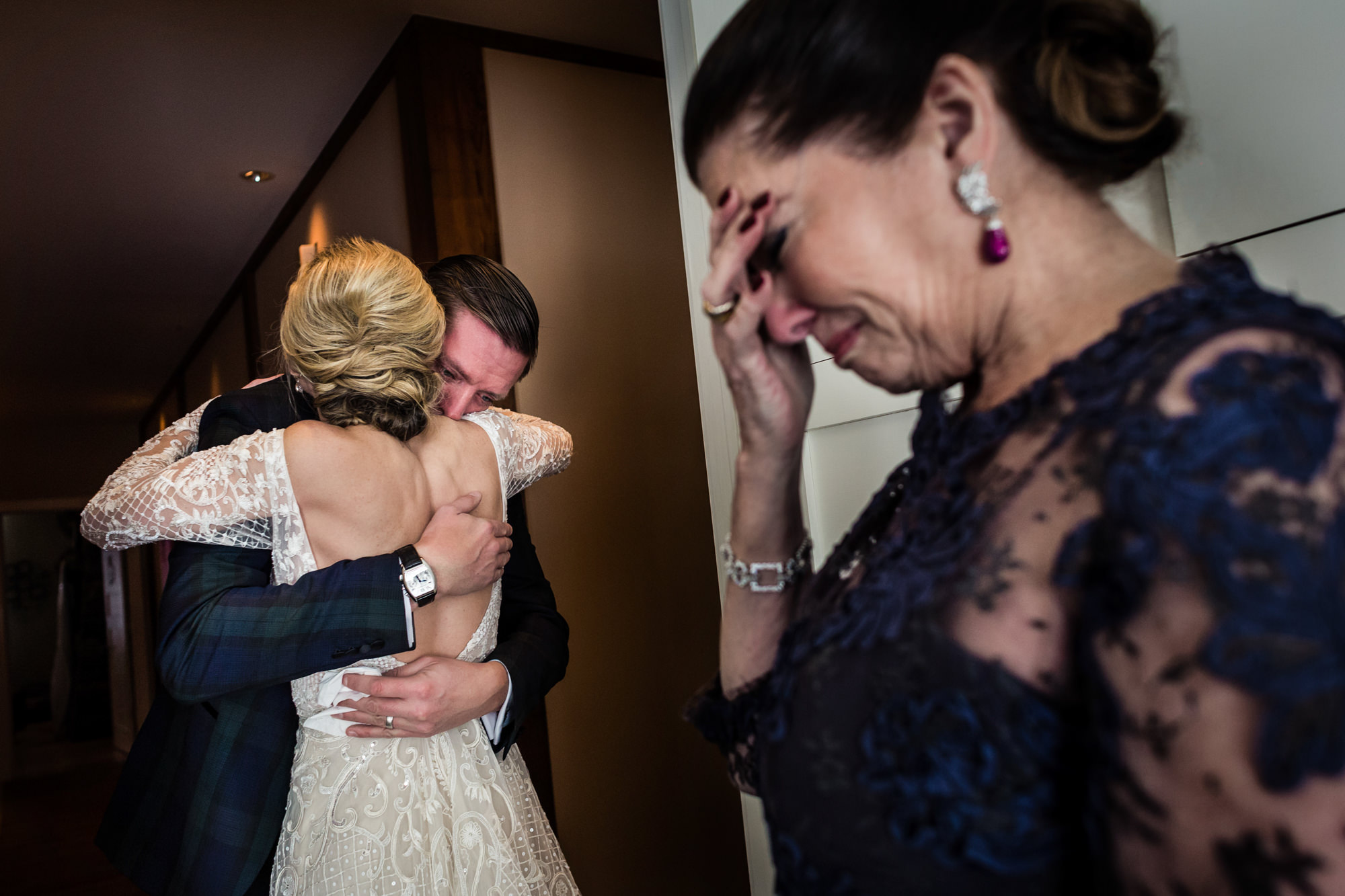 Emotional bride's mom and bride hugging dad - photo by JAG Studios
