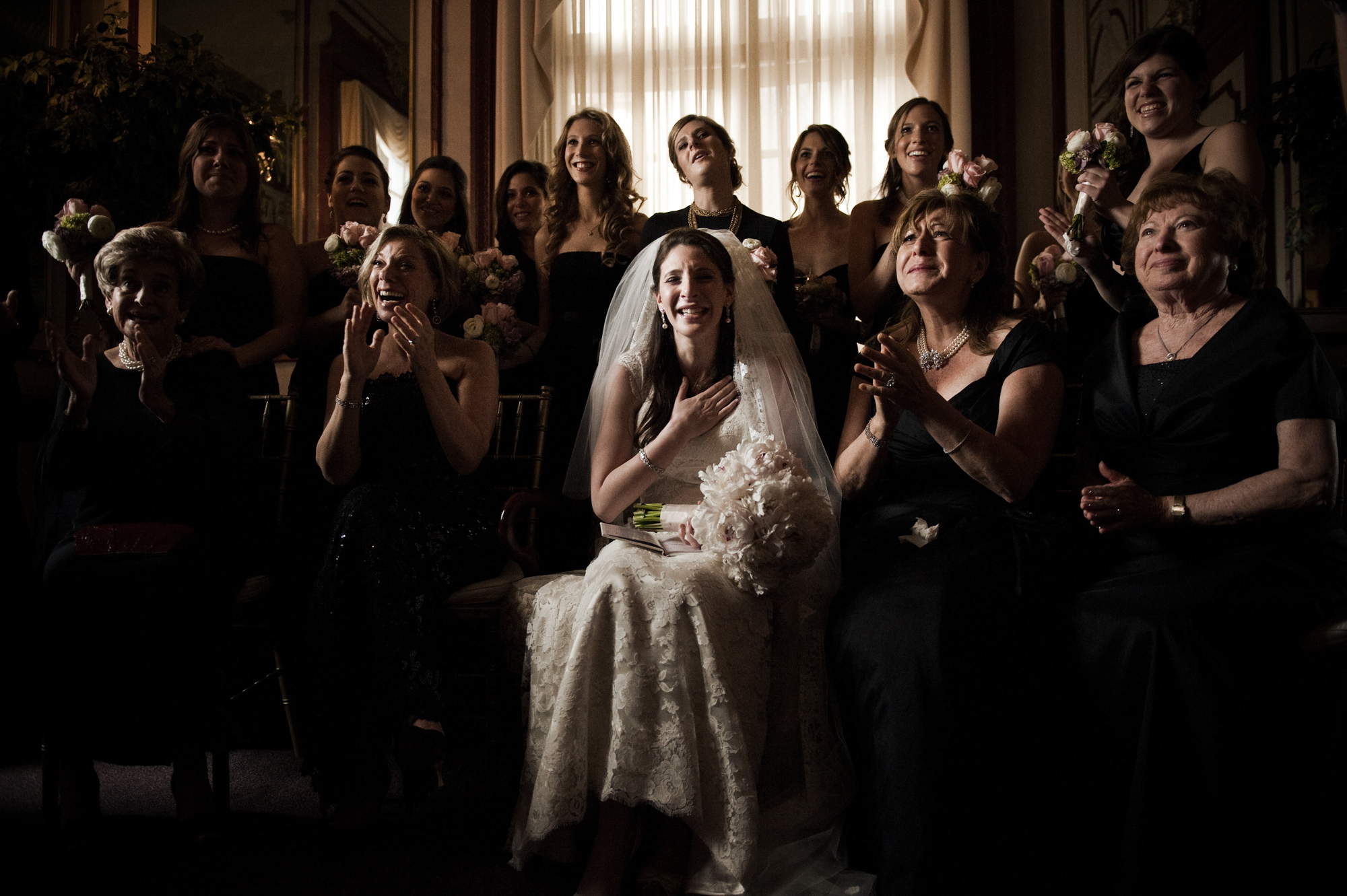 Emotional bride surrounded by women photo by Cliff Mautner