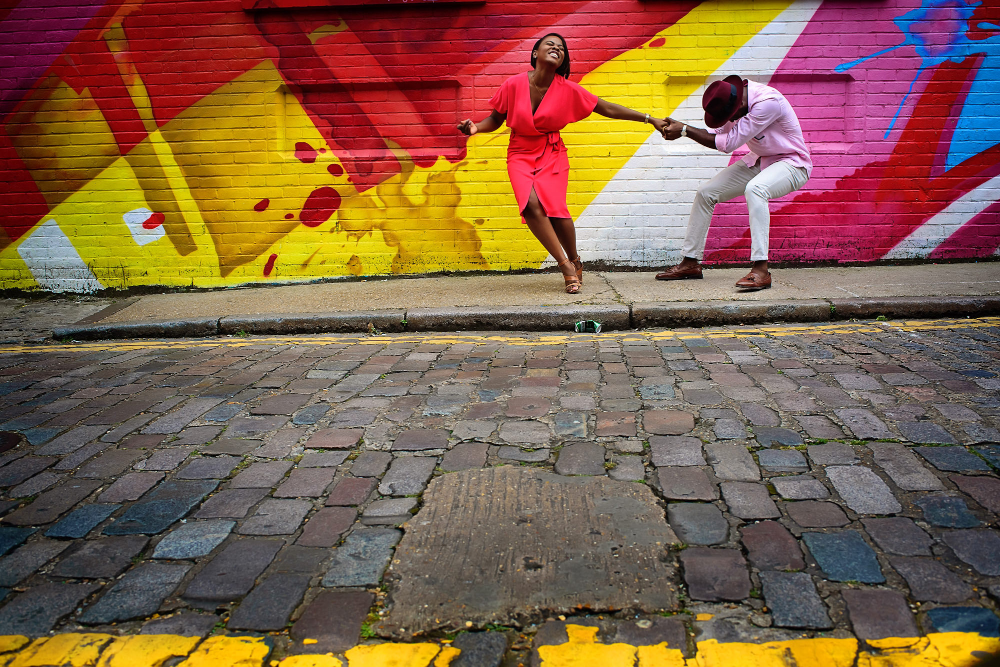 Engagement couple playing in front of mural - photo by Alakija