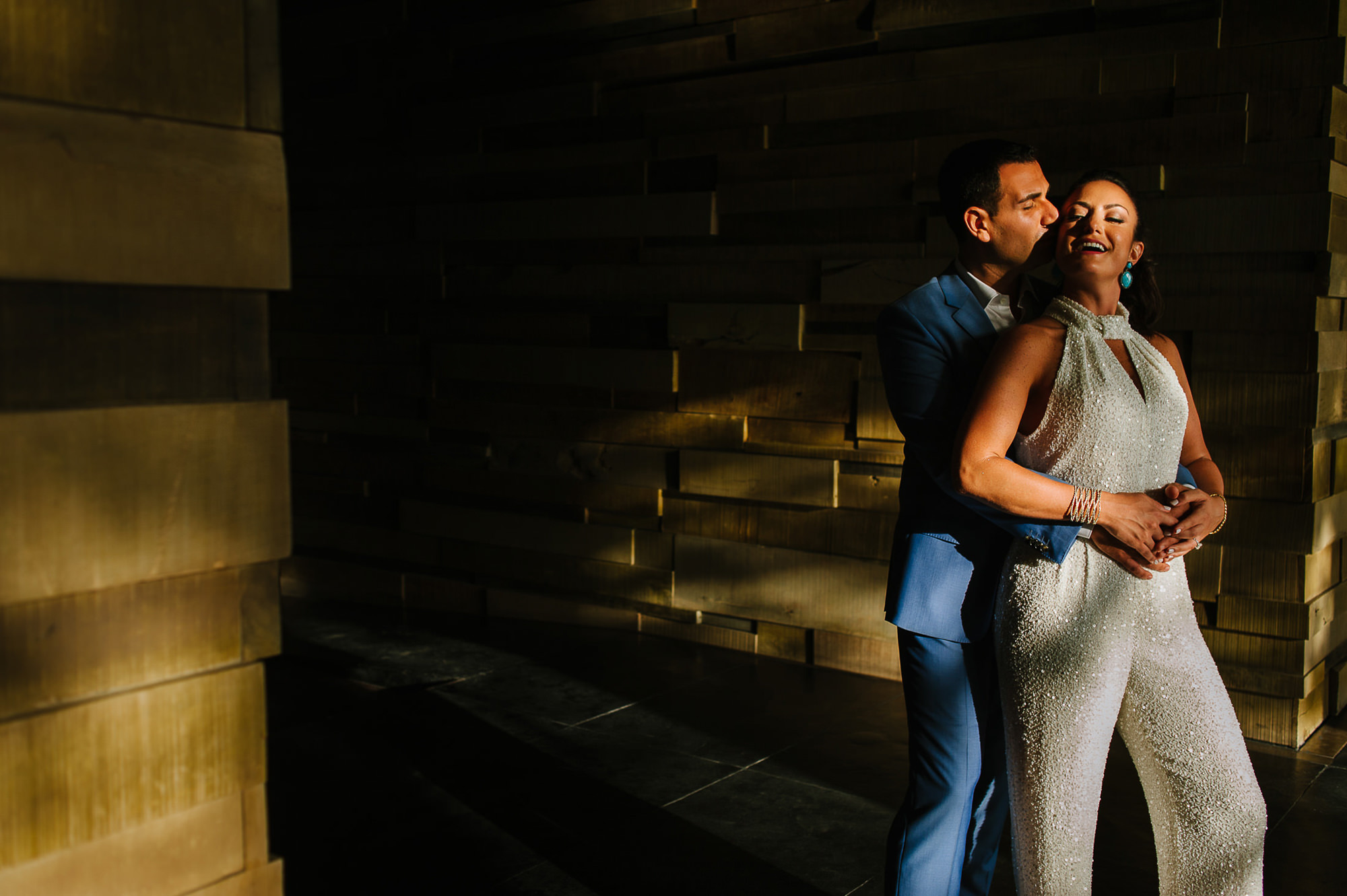 Bride in shimmering halter-neck pantsuit and groom in blue suit embrace, by Citlalli Rico