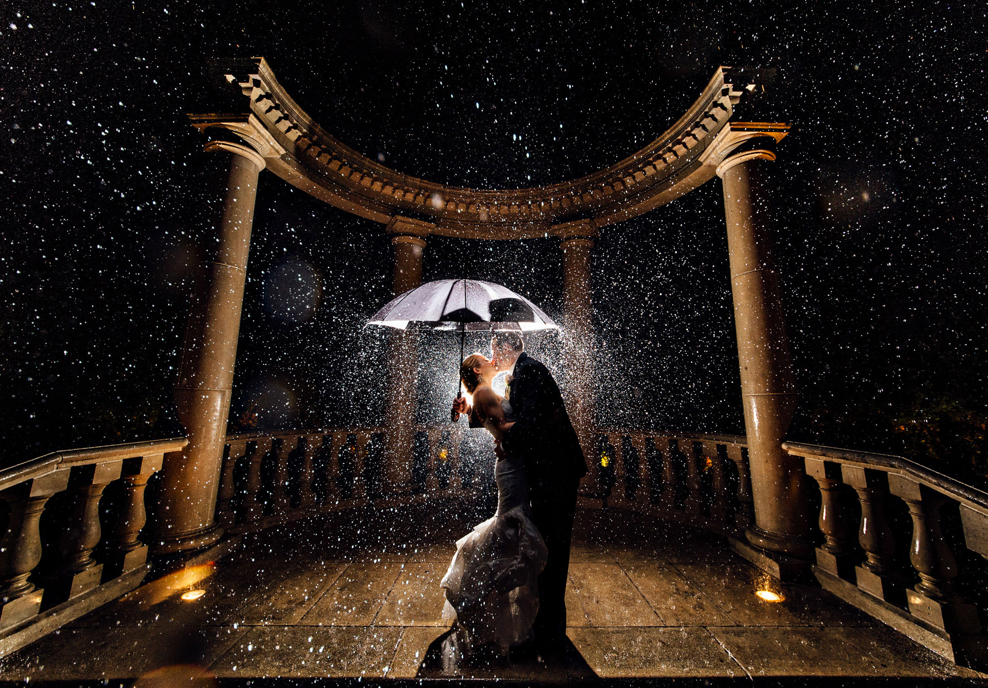 Dramatic photo in the rain of couple under umbrella with flash, by The Brenizers