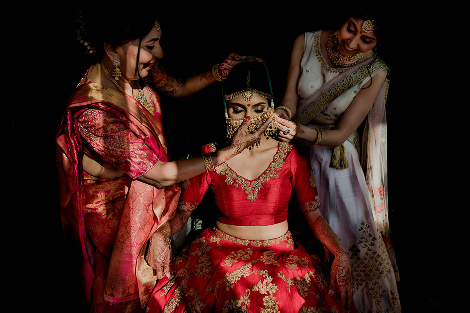 Family placing jewelry on Indian bride wearing red sari image by Rimi Sen
