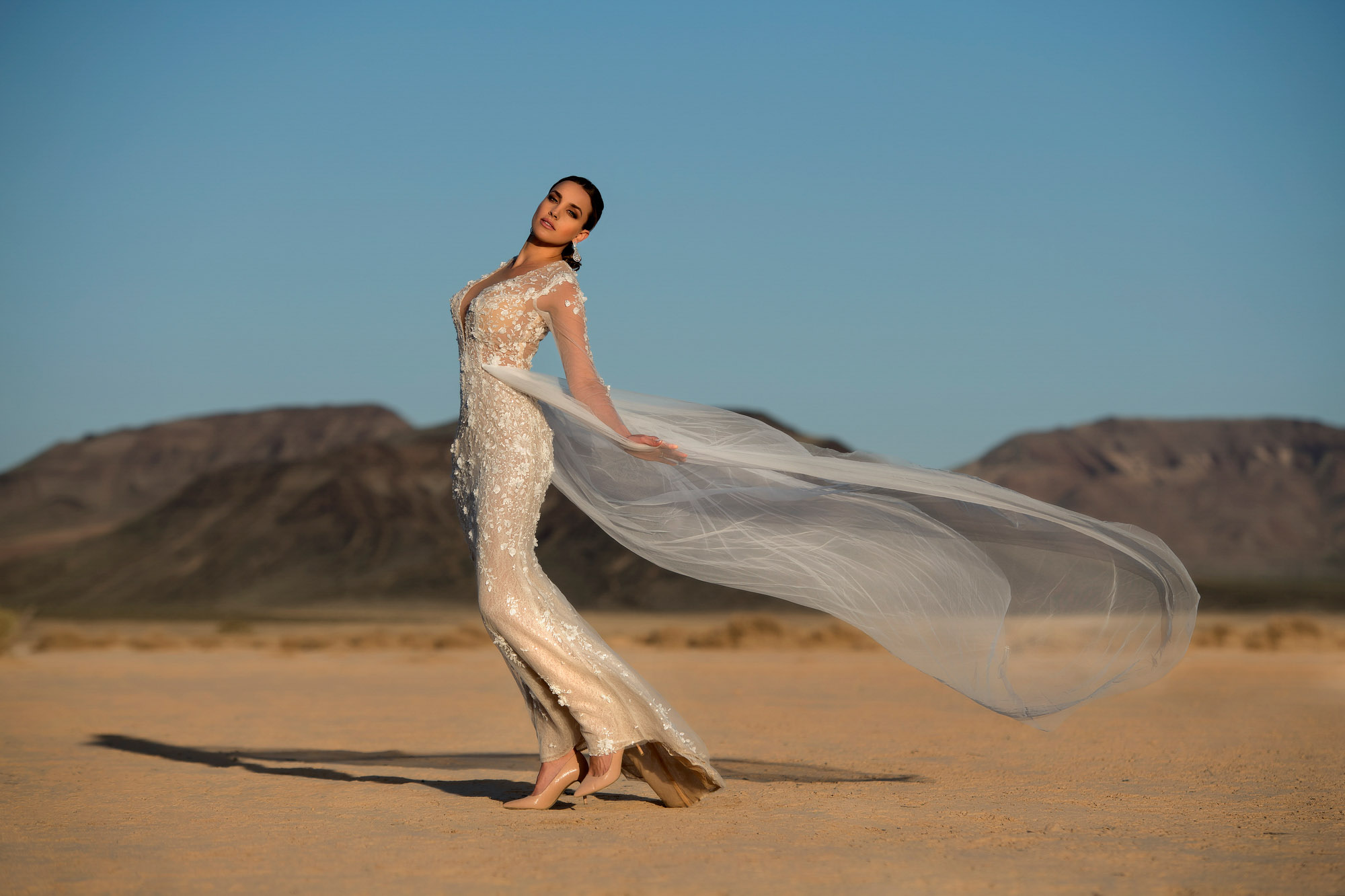 Bride wearing lace dress with tulle train in desert - photo by Jerry Ghionis - Nevada and Australia