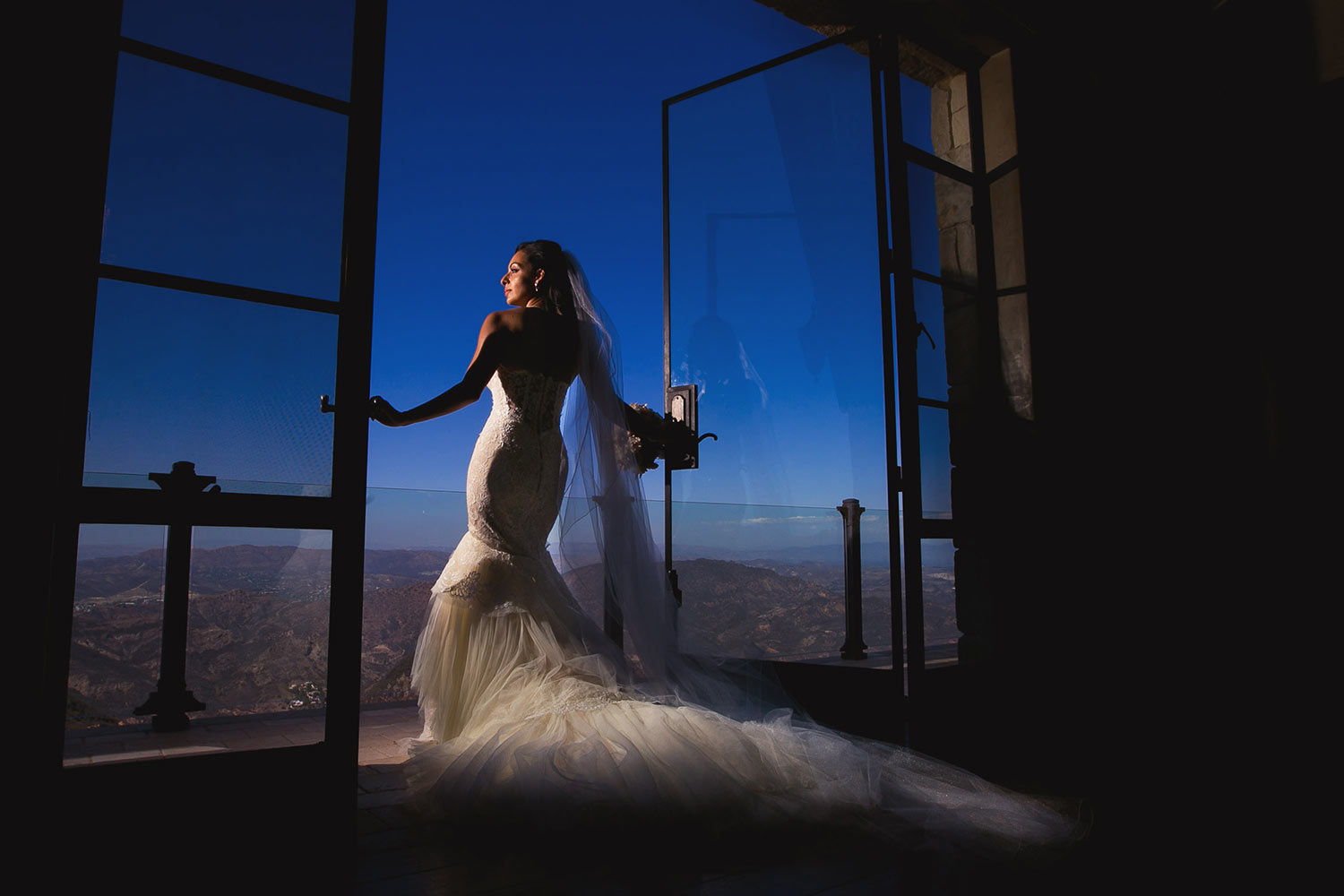 Moody elegant bride in trumpet tulle gown on balcony by Callaway Gable