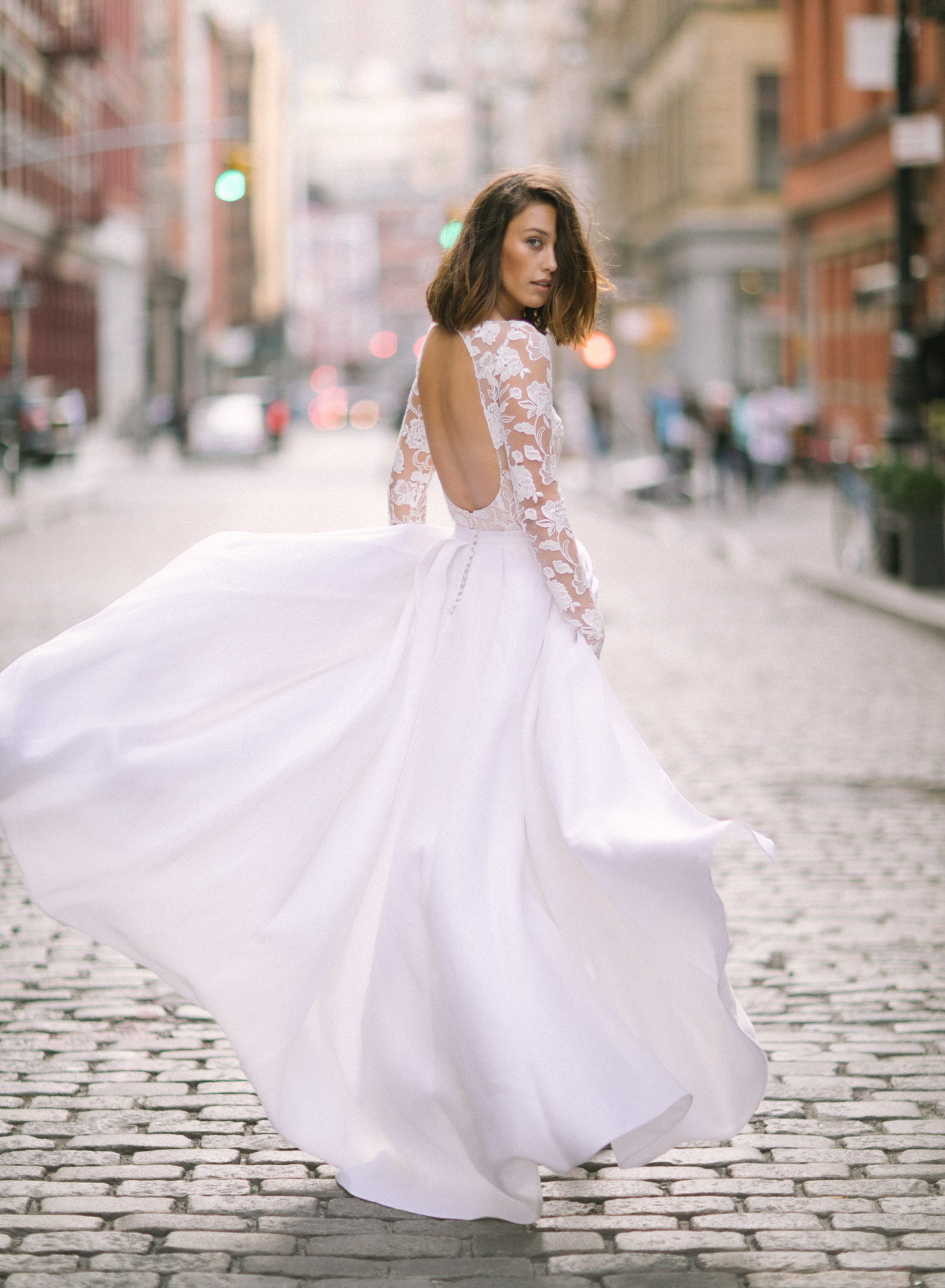 Bride in backless long-sleeve lace gown, by Greg Finck