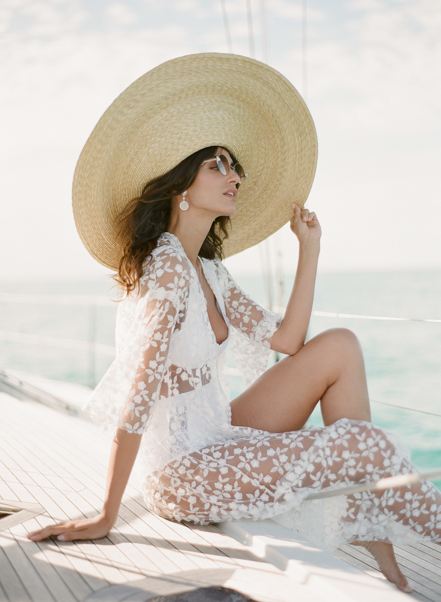 Fashionable bride with large straw hat lace cover up on yacht - Greg Finck Photography