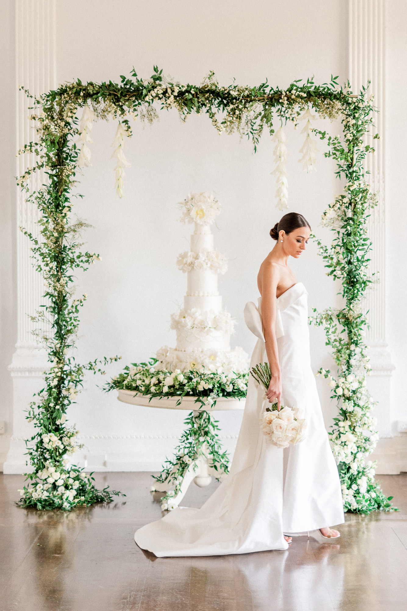 Bride with fondant floral cake and greenery arbor - photo by Gianluca Adoviaso Photography