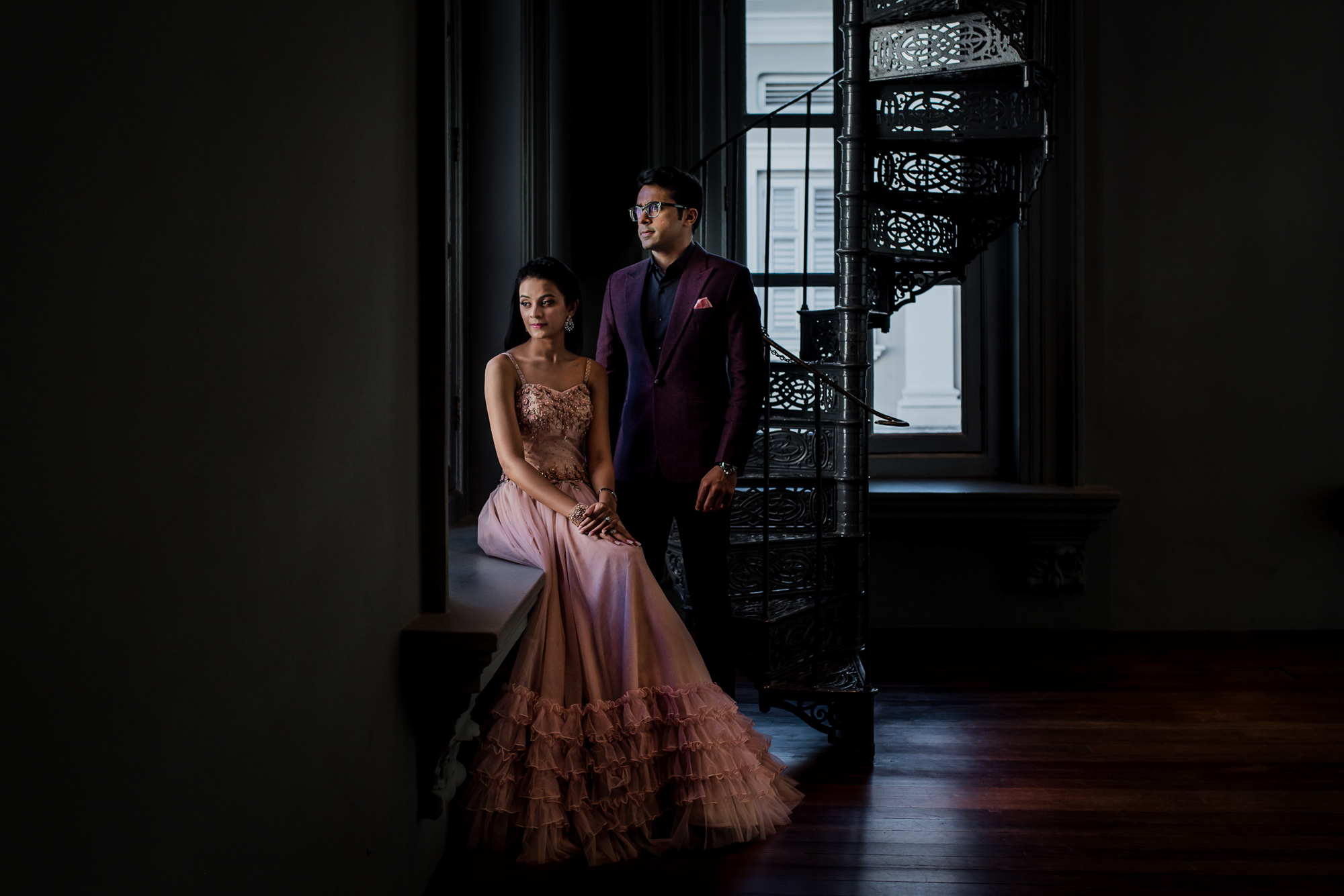 Bride in pink gown and groom in plum suit by window image by Rimi Sen